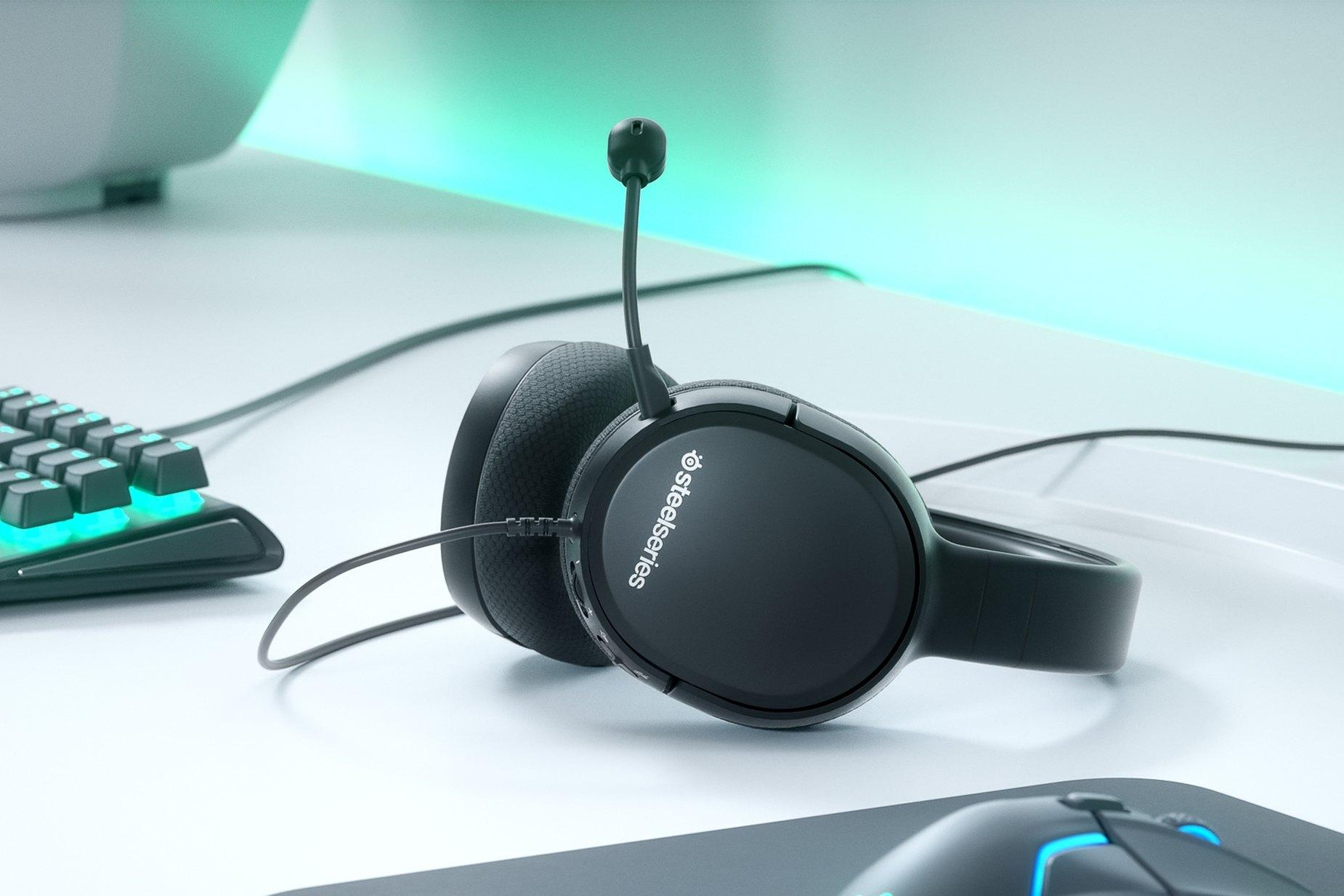 Arctis 1 遊戲耳機放置桌面,還有 SteelSeries 整套裝備包括滑鼠,滑鼠墊,和鍵盤。