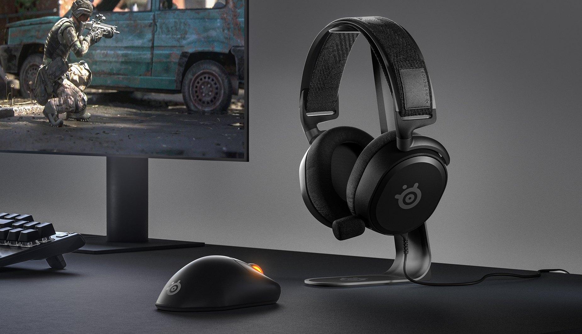 桌上型電腦配備,搭配螢幕、鍵盤、滑鼠與放置在台面上的 Arctis Prime 耳機。