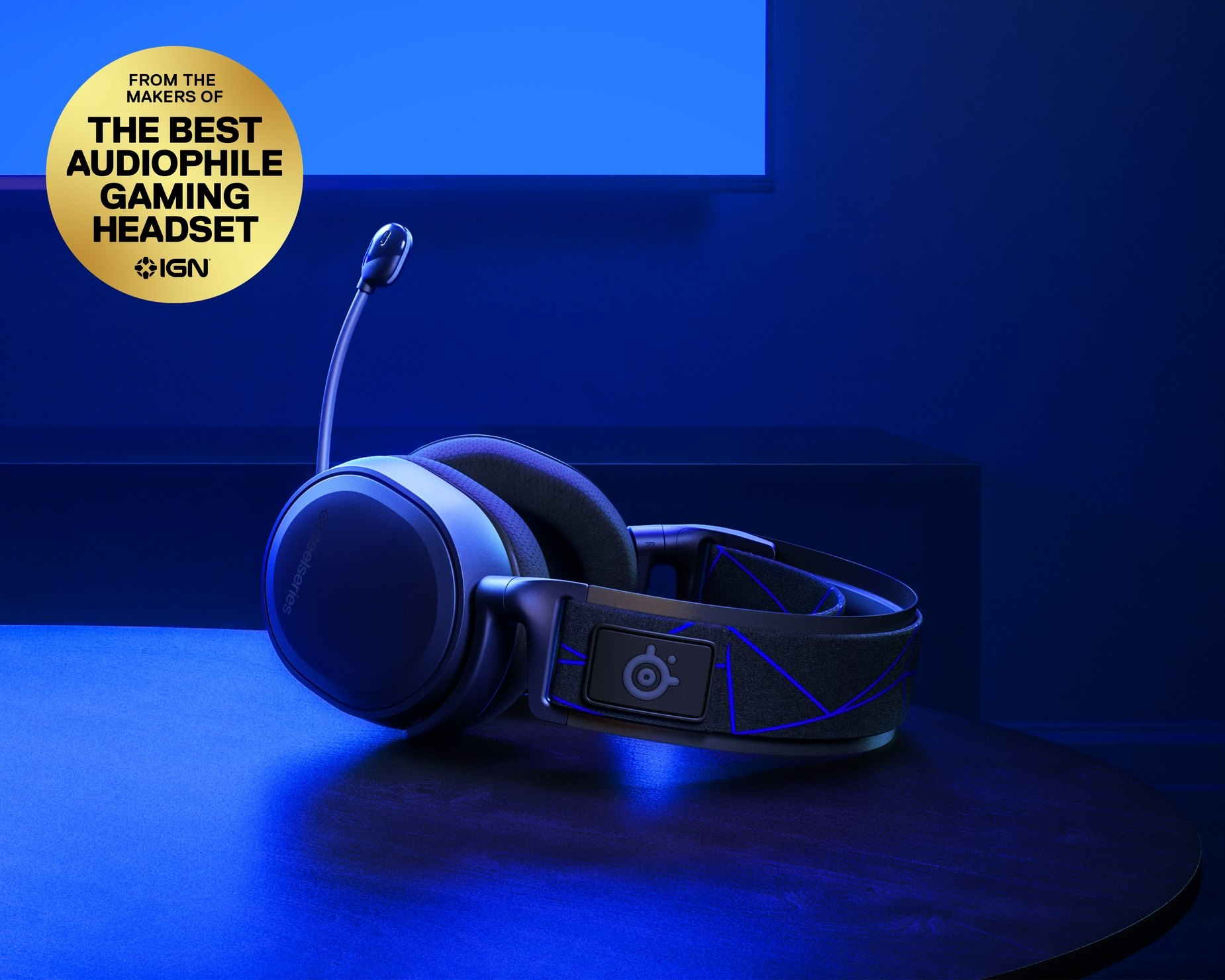 Arctis 7P耳機平放於桌面上並且麥克風呈現打開的位置。可以看到 PlayStation 的招牌色調。