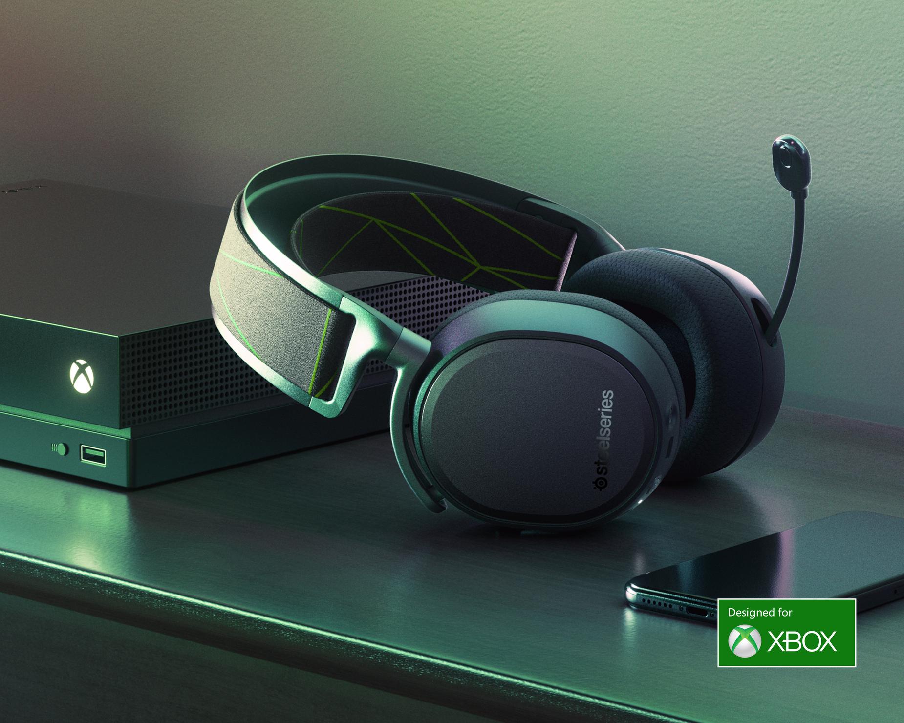 Arctis 9X 靠在一台 Xbox One 主控台上,連接的麥克風呈開延狀態