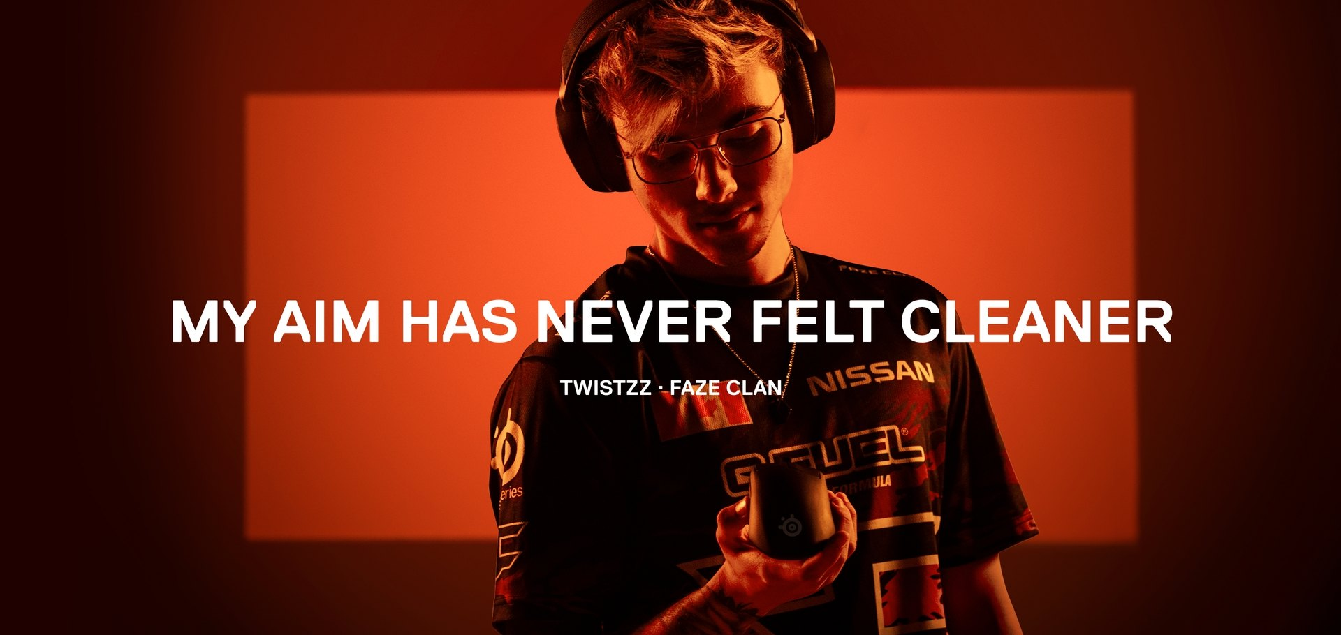 FaZe 玩家 Twistzz 站在橘色背景之前,手上拿著 Prime 滑鼠。圖片上的字樣為:「我的瞄準度從未如此精確過。」