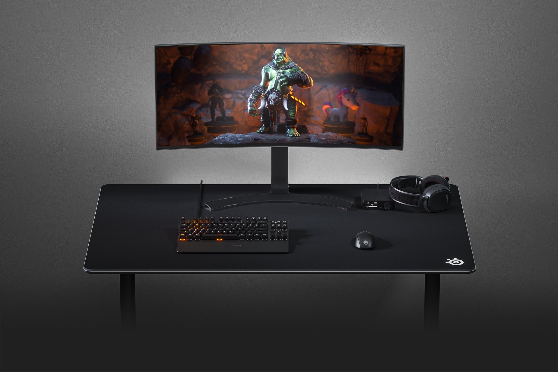 SteelSeries 4XL gaming mousepad on a desk with a monitor, headset, mouse, and keyboard