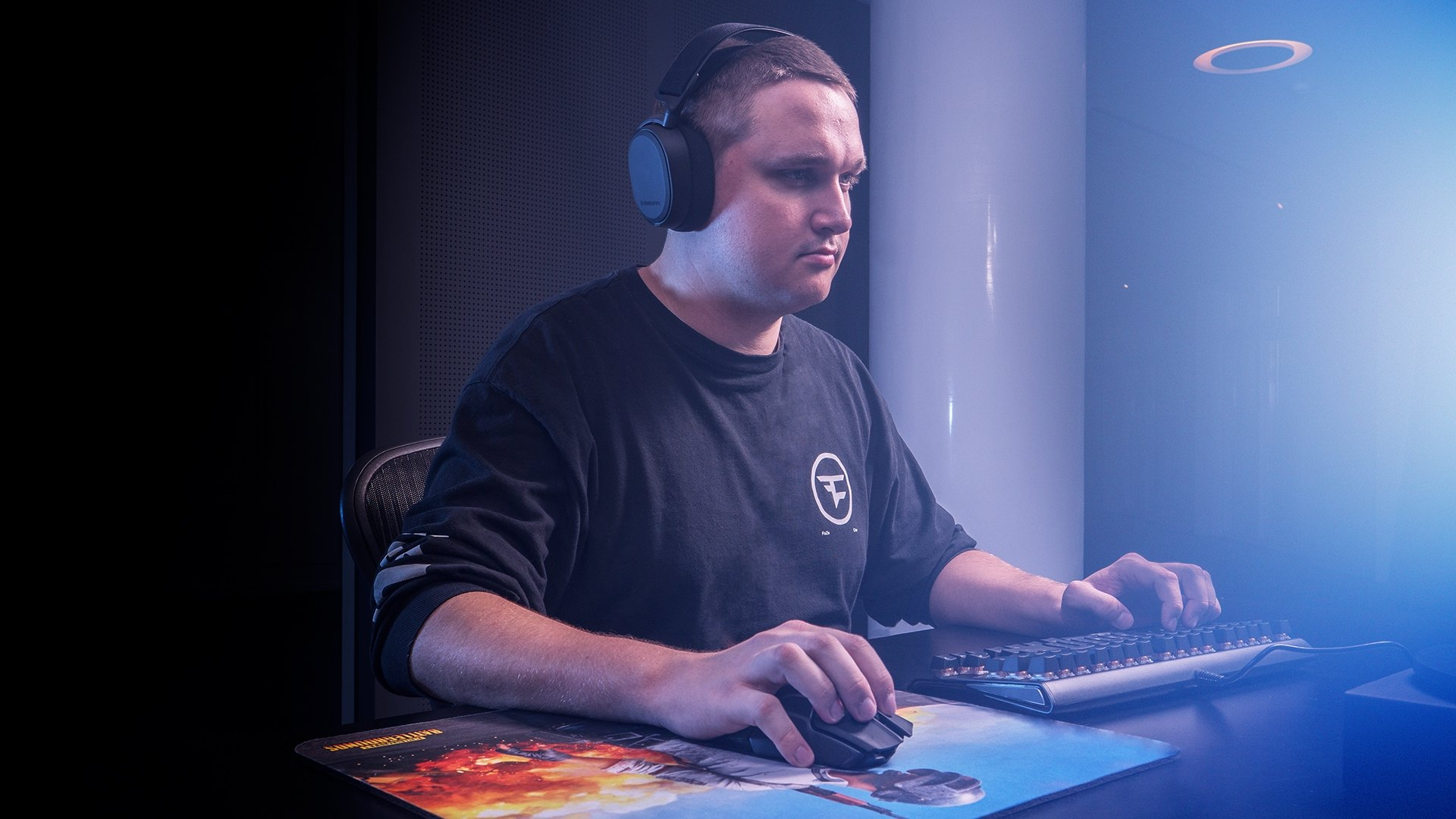 "FaZe Clan PUBG player Anssi ""mxey"" Pekkonen plays a game on the computer wearing a FaZe Clan shirt and SteelSeries Arctis headphones. He grips the keyboard with one hand and a wireless mouse in the other, using a large PUBG branded mousepad."