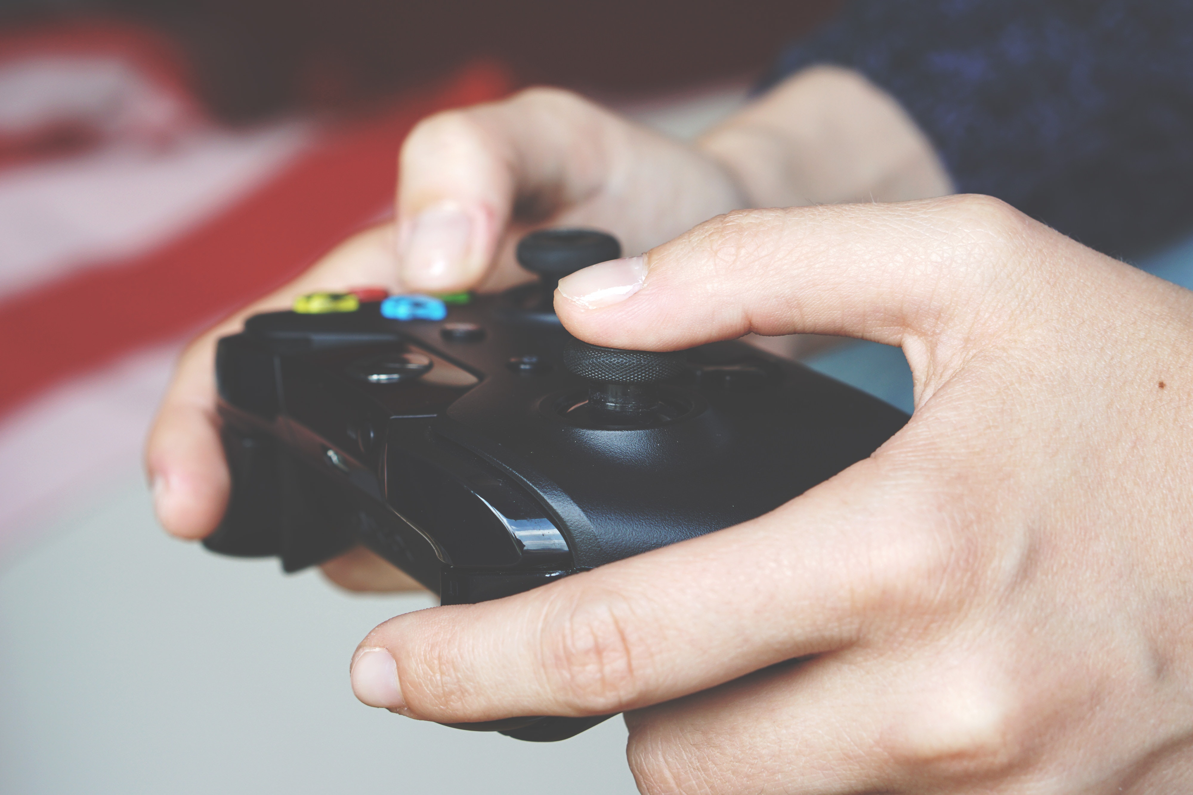 A person's hands holding an Xbox One controller, pressing the left trigger and A button simultaneously