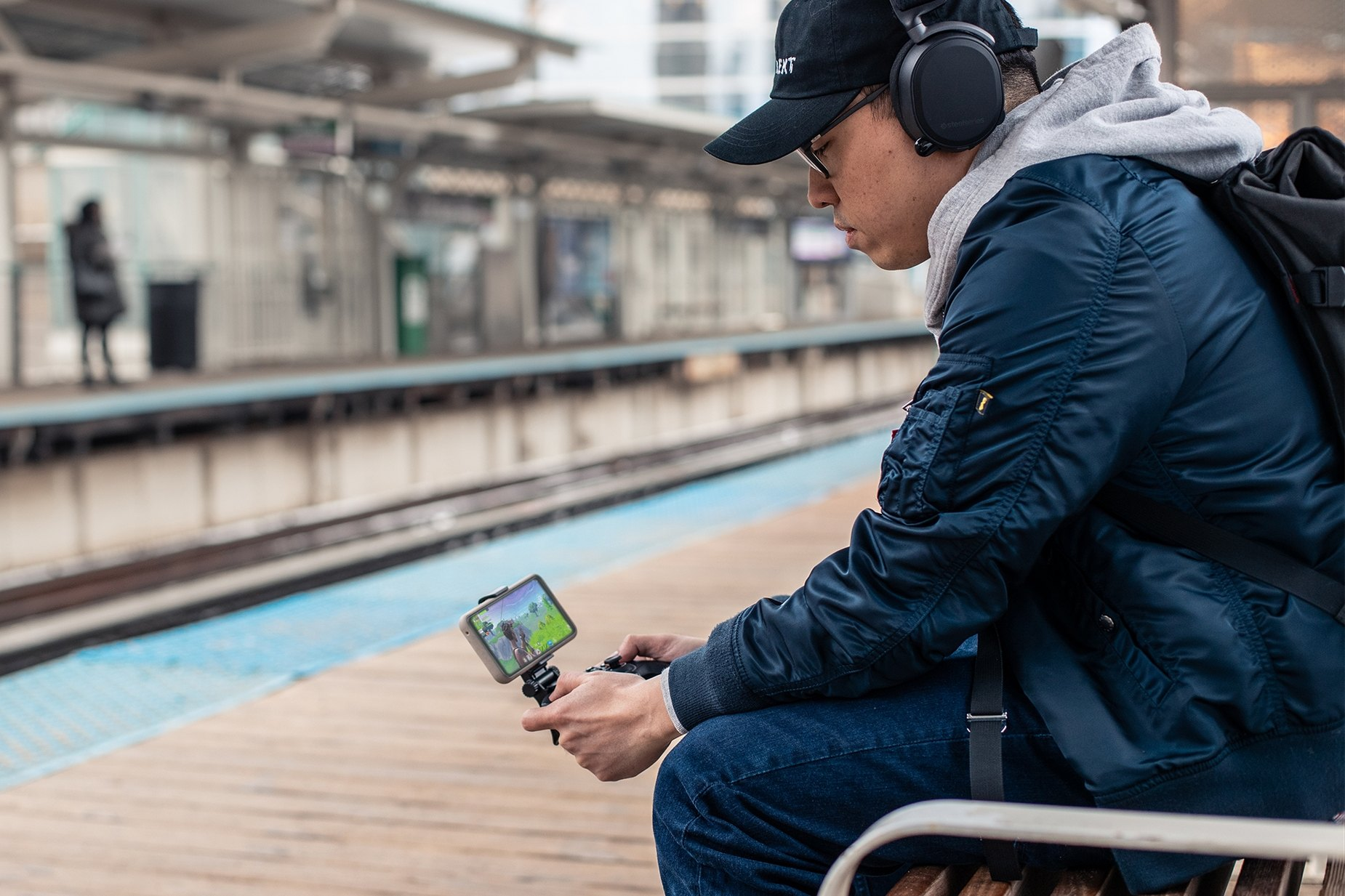 Man sitting on a bench wearing SteelSeries headphones playing a mobile game using a SteelSeries controller and SmartGrip accessory
