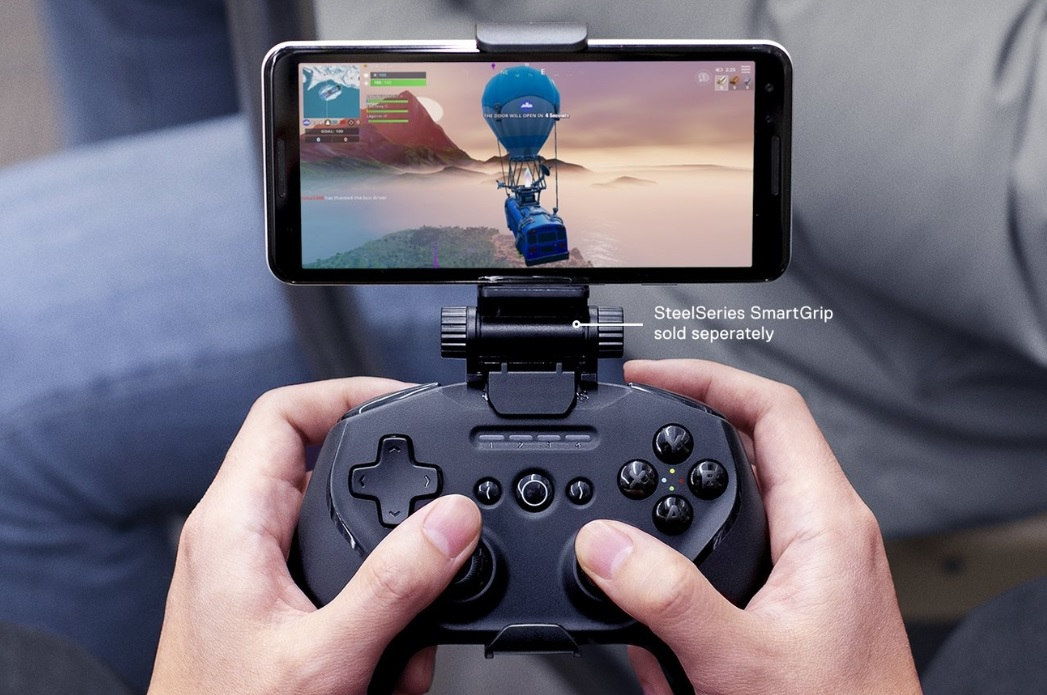 "Hands playing a mobile phone game with a controller, connected by a SteelSeries SmartGrip accessory with text ""SteelSeries SmartGrip sold separately"""