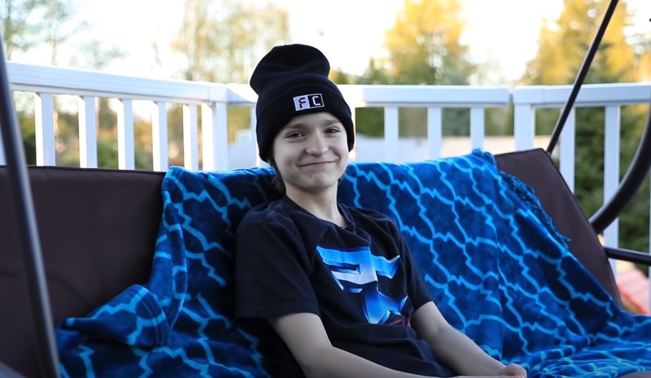 FaZe H1ghSky1 sits, smiling on a porch swing.