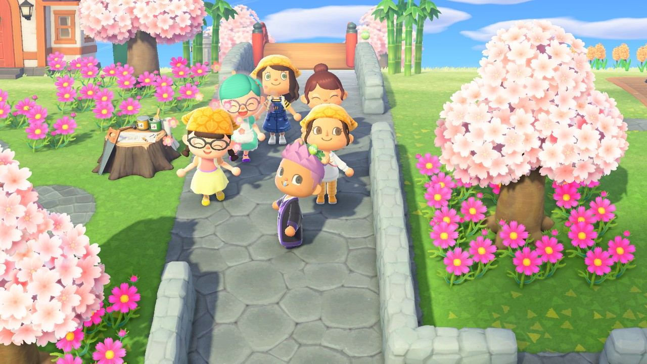 Six smiling characters gather on a path surrounded by cherry blossoms in the game Animal Crossing New Horizons