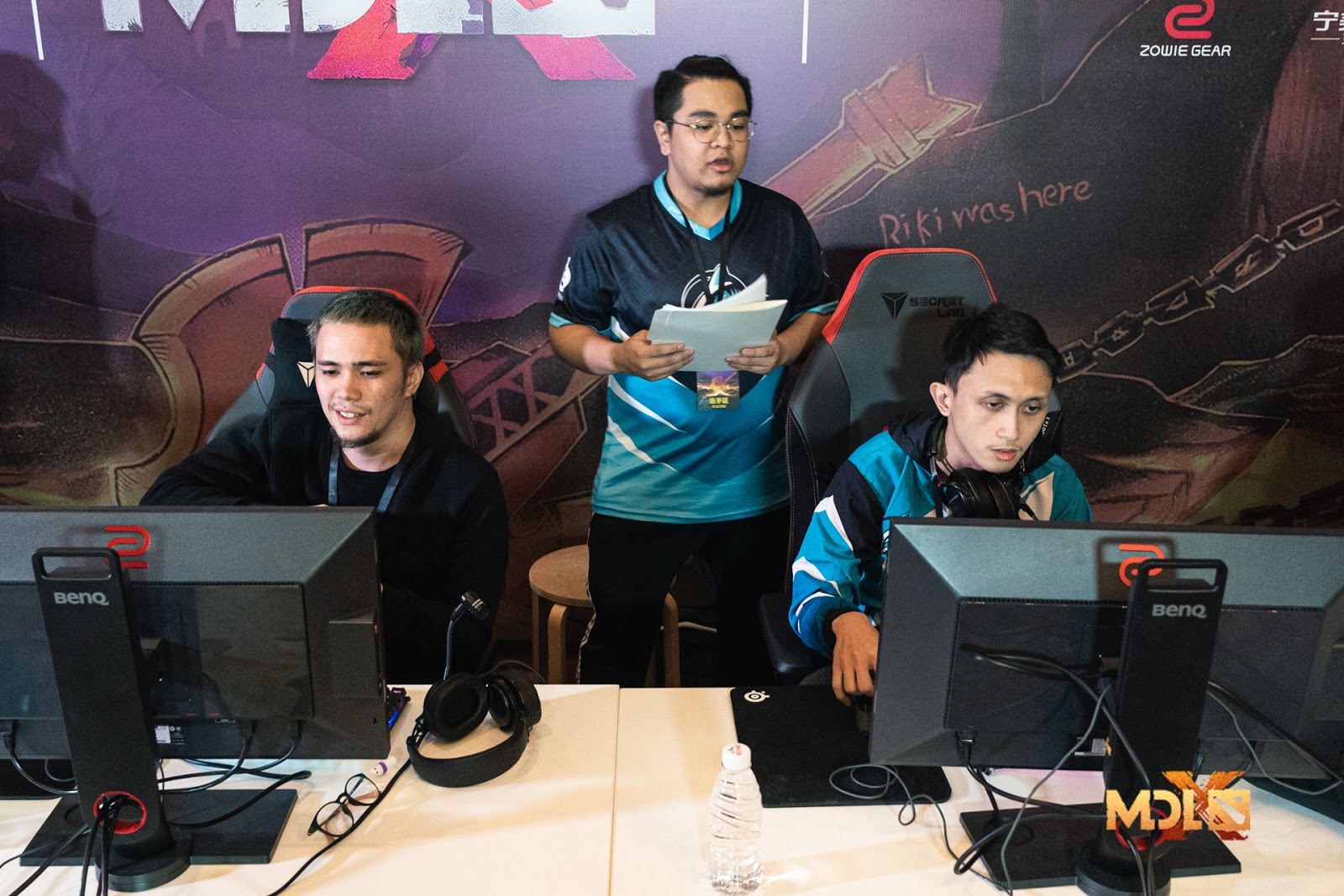 2 Team Adroit players sitting in a tournament booth with their coach behind them