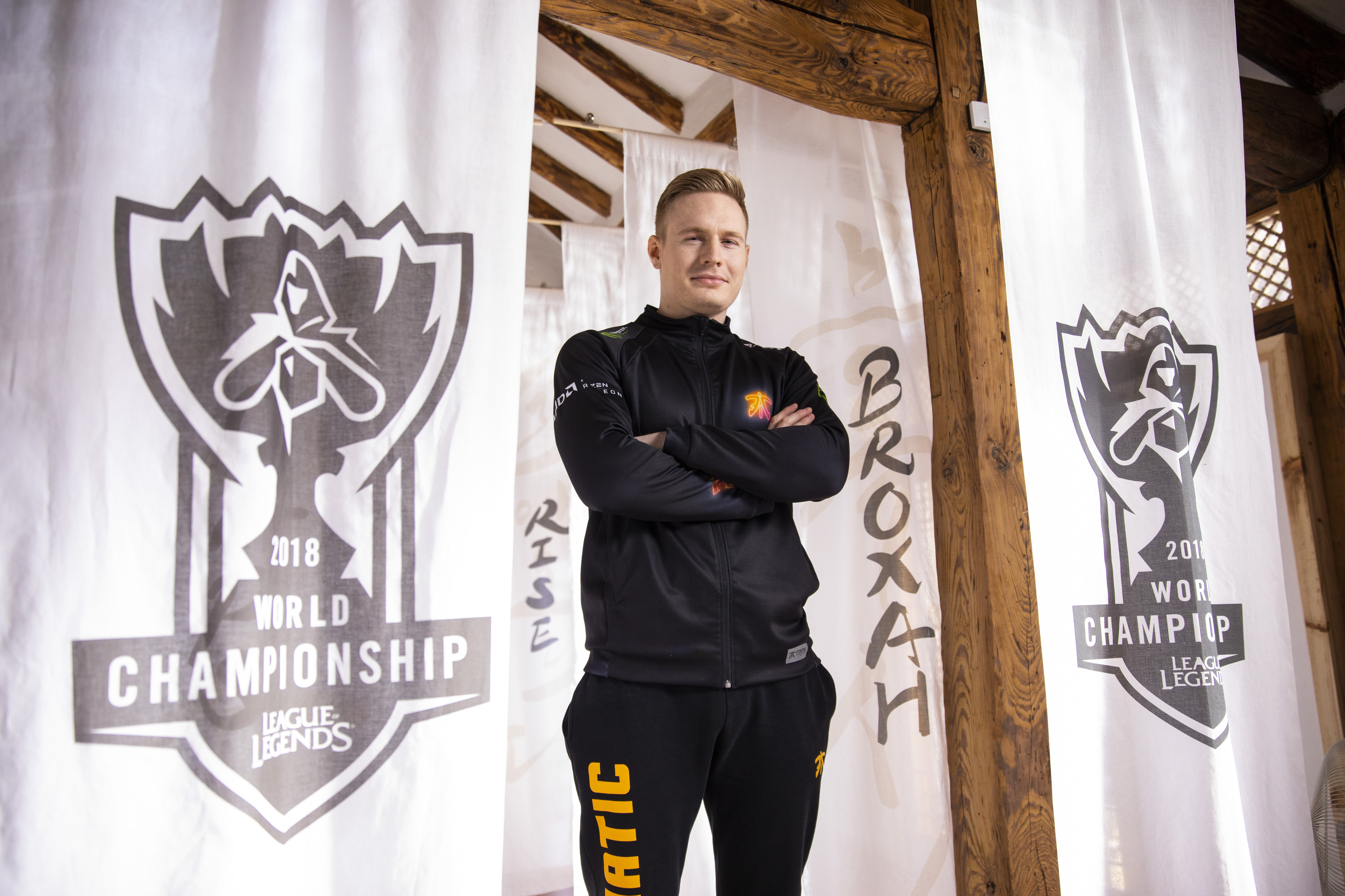 "Mads ""Broxah"" Brock-Pedersen surrounded by League 2018 World Championship banners"