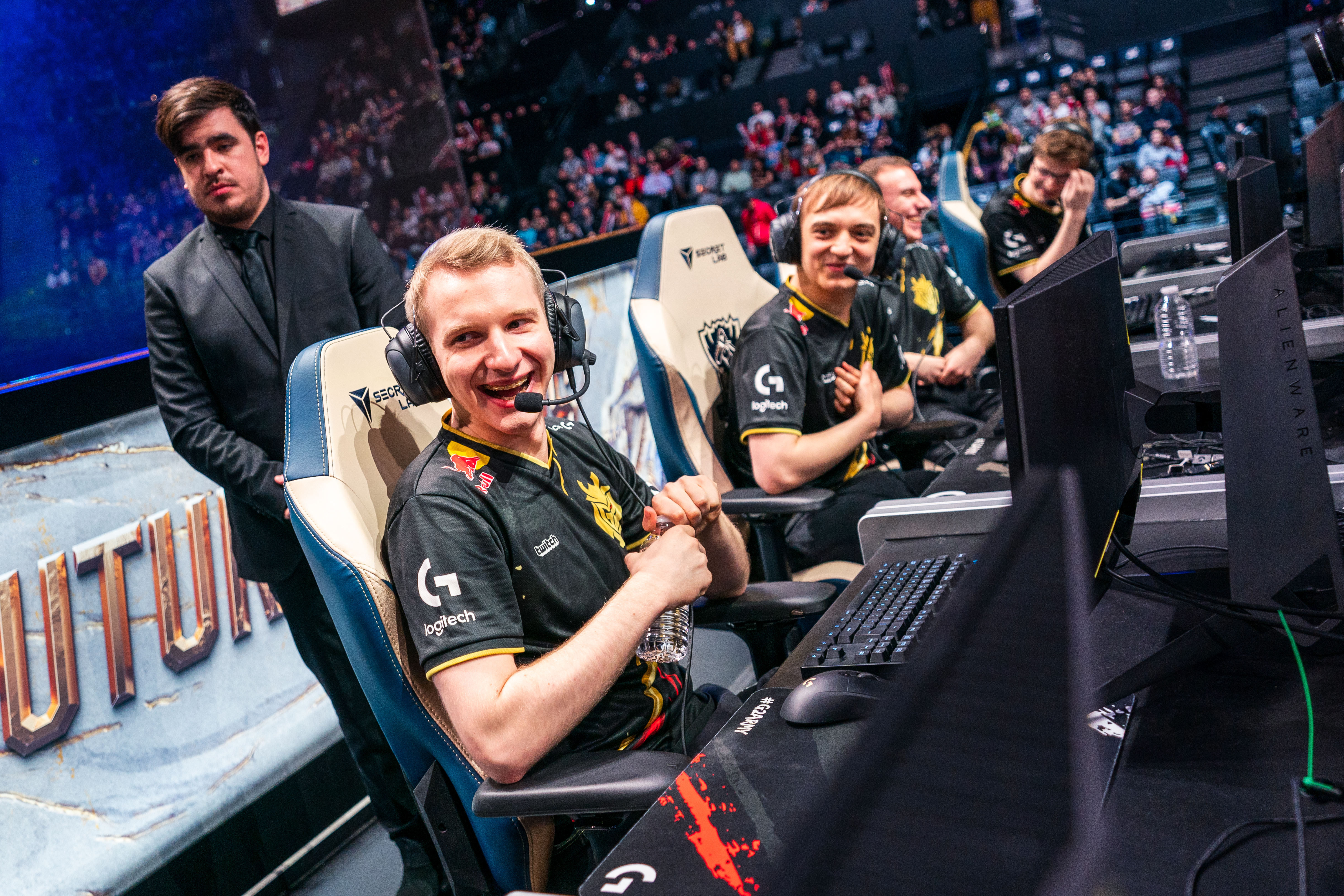"G2's jungler Marcin ""Jankos"" Jankowski smiling while sitting with his team on an esports stage"