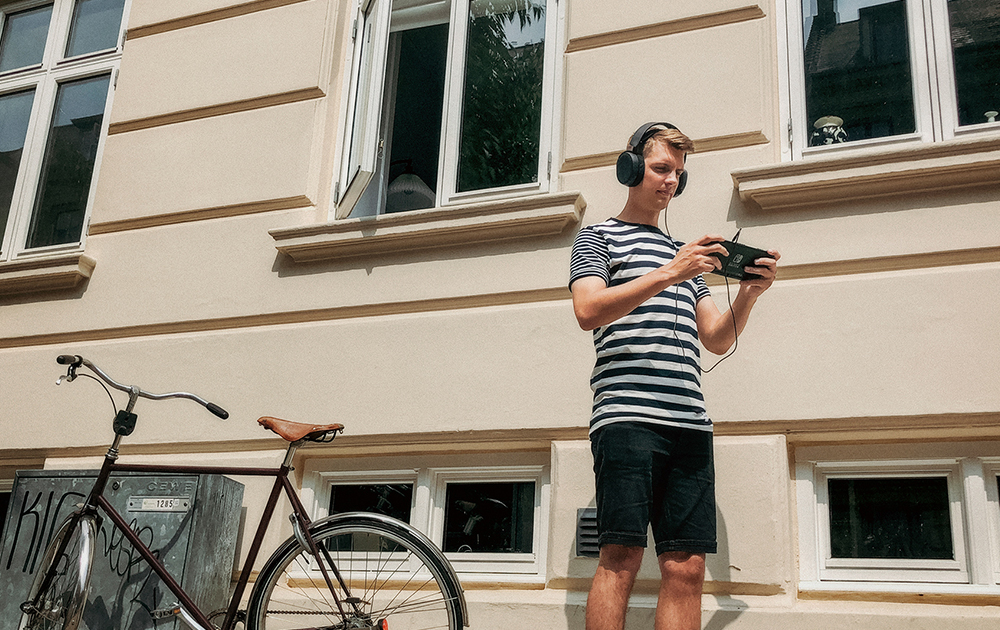 Man wearing Arctis 3 headset playing on Nintendo Switch outdoors