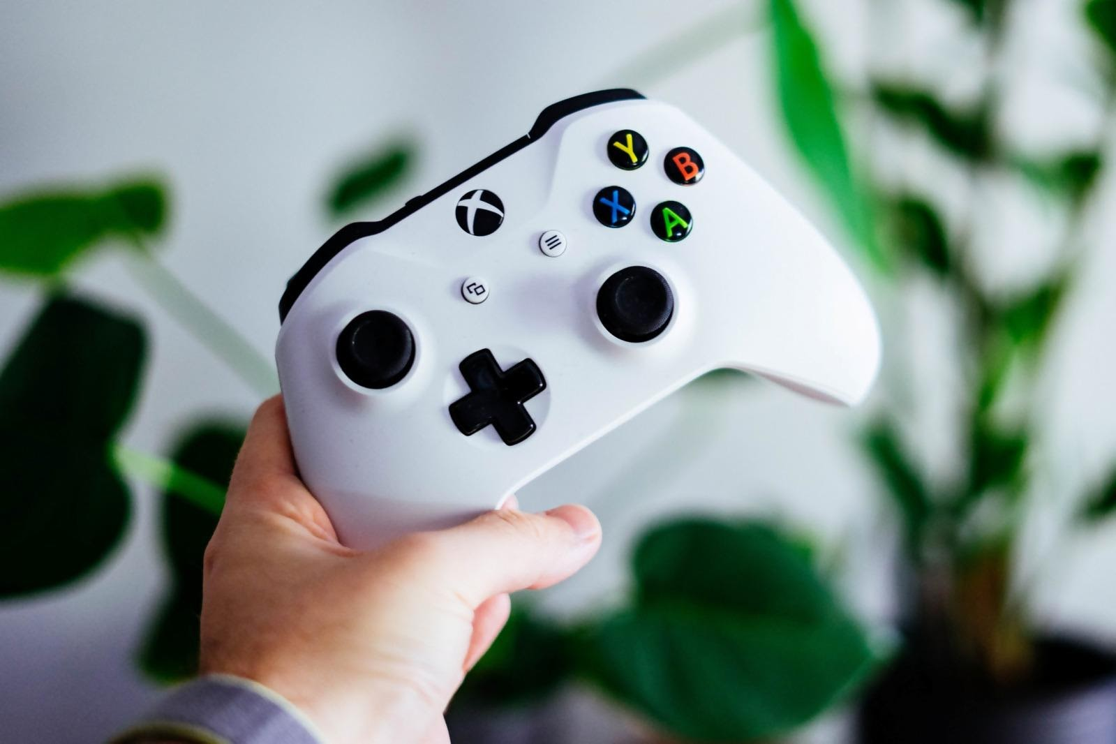 stock photo of a hand holding a white Xbox One controller with a blurred green plant in the background