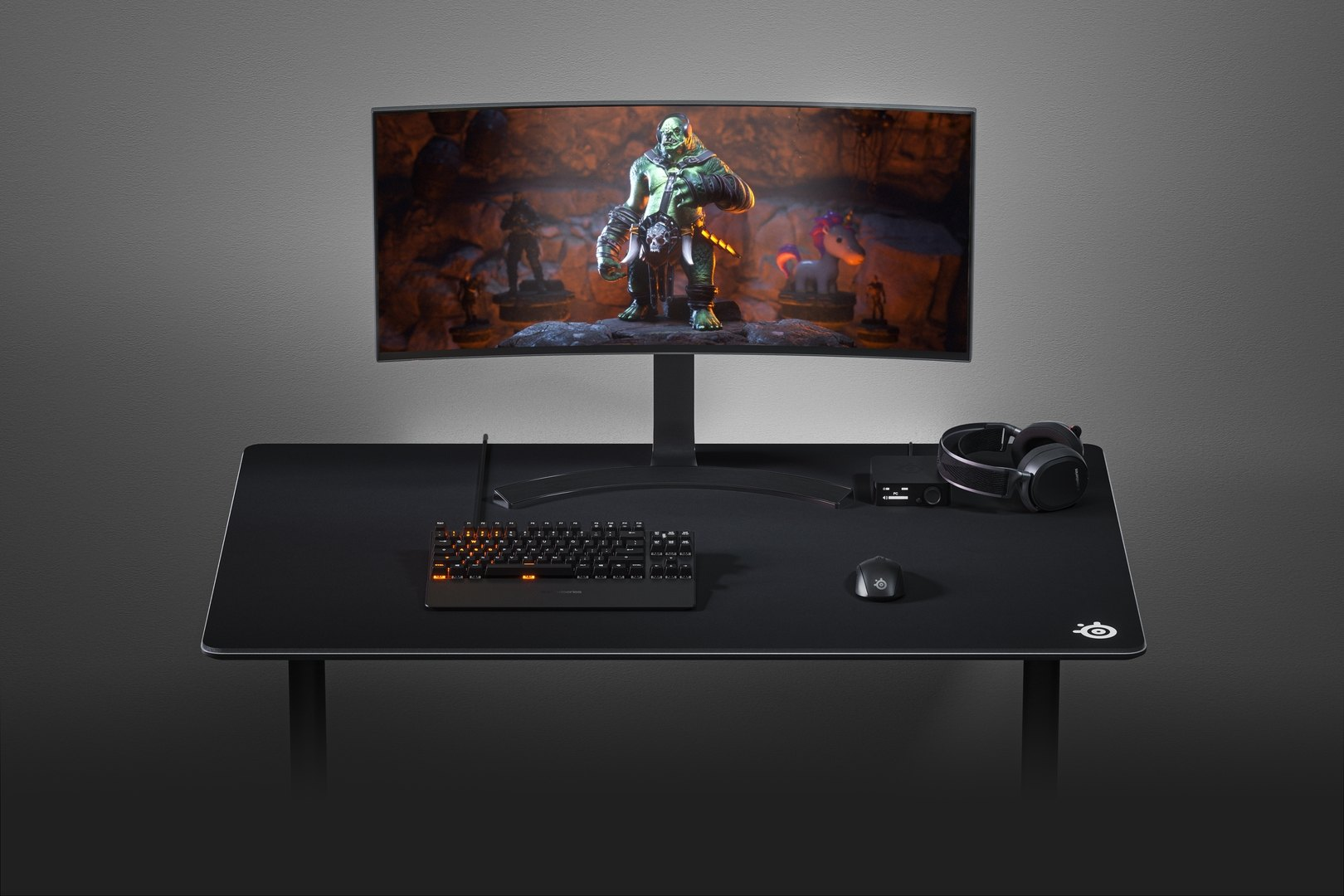 QcK 4XL mousepad on a PC gaming desk with a monitor, keyboard, headset, and mouse