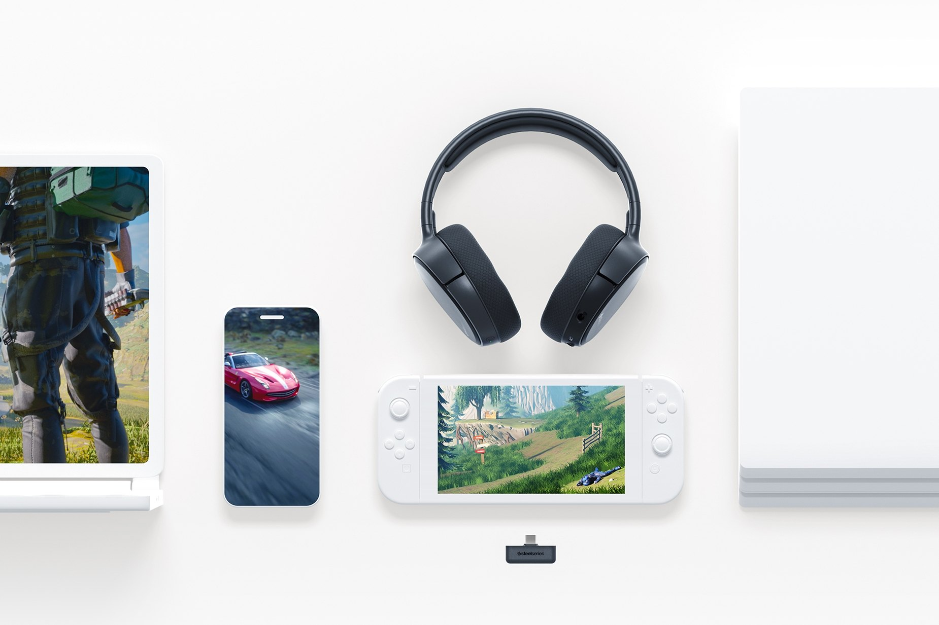 Arctis 1 Wireless for Switch headset laying on a plain table with a mobile phone, Switch, console, and tablet