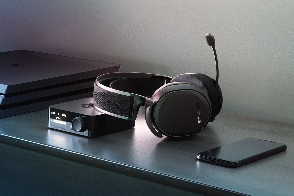 An Arctis Pro Wireless headset and it's transmitter box on a table next to a mobile phone and PlayStation 4 console