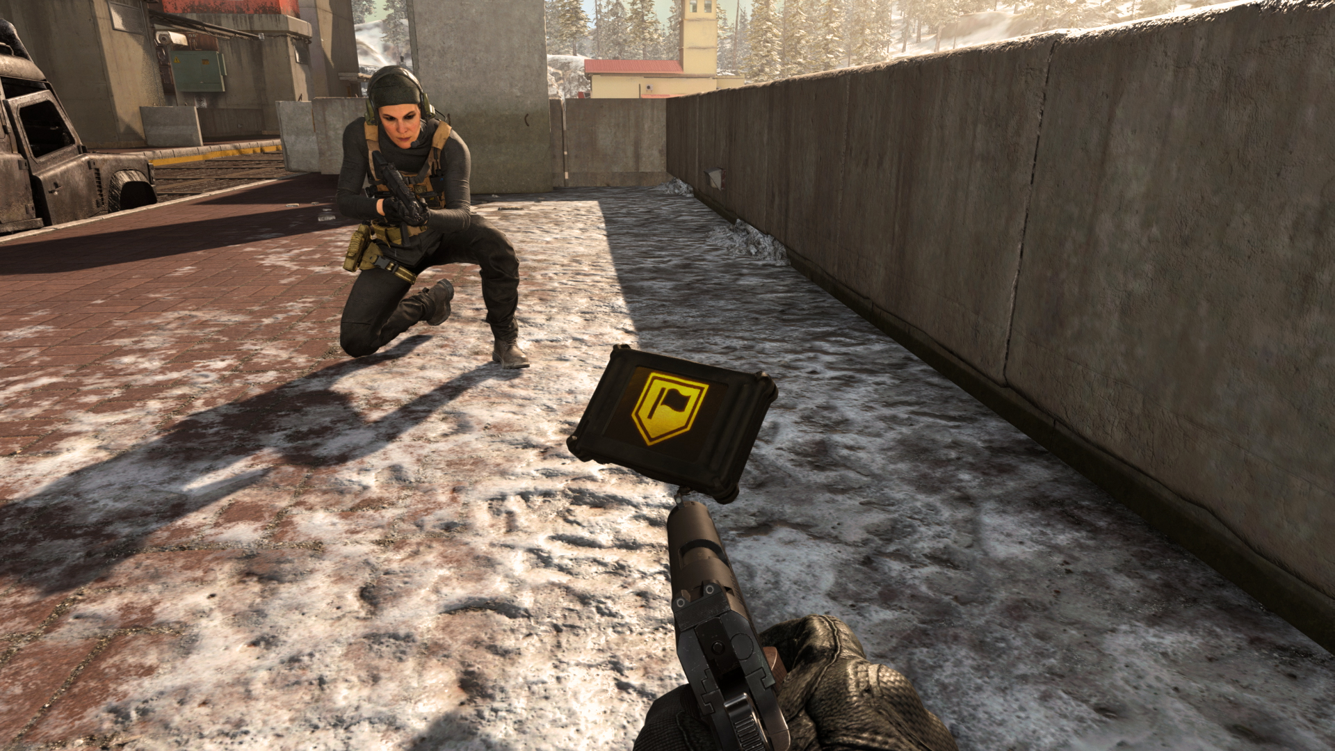 A female soldier crouches next to a hovering black box with a yellow flag symbol on it.