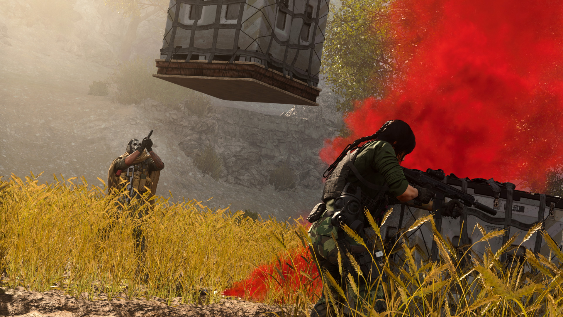 Two soldiers stand in a field, rifles raised, next to a rising plume of red smoke. A supply crate sits on the ground and another is being lowered to them below.