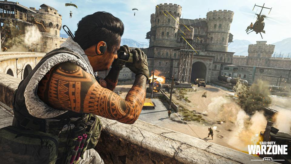 A heavily tattooed soldier looks through binoculars over a wall as a battle rages below, featuring gun fights and a helicopter with a castle in the background.