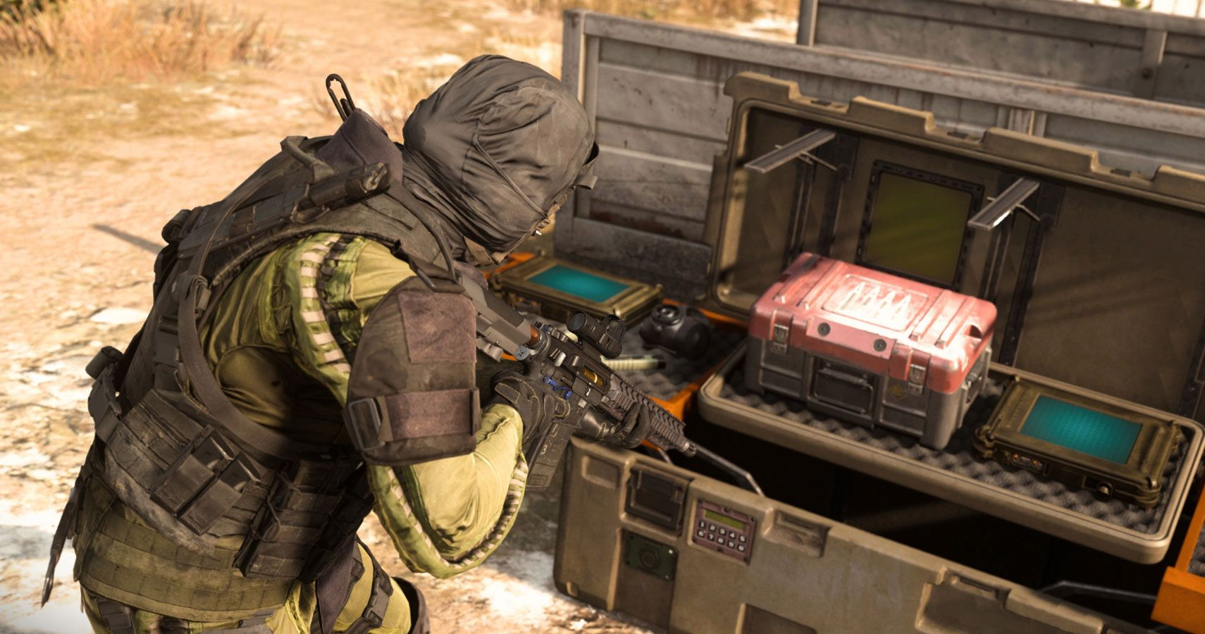 A soldier crouches next to an open supply crate with a red box and two devices with screens