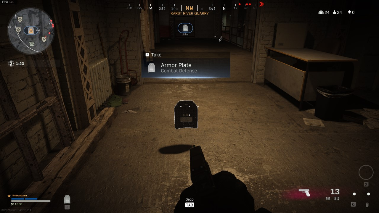 "A first person view of a darkened room. An armor plate hovers above the ground, with a text box reading ""Armor Plate, Combat Defense"" and an ""F"" symbol with the word ""Take."" A circular map is in the top left corner of the screen, with a simulated compass across the top of the screen. The bearing is NW ""Karst River Quarry."" A Heads up Display in the bottom right hand corner shows a pistol with 13/30 rounds. At the bottom of the screen is a Tab symbol with the word ""Drop."""