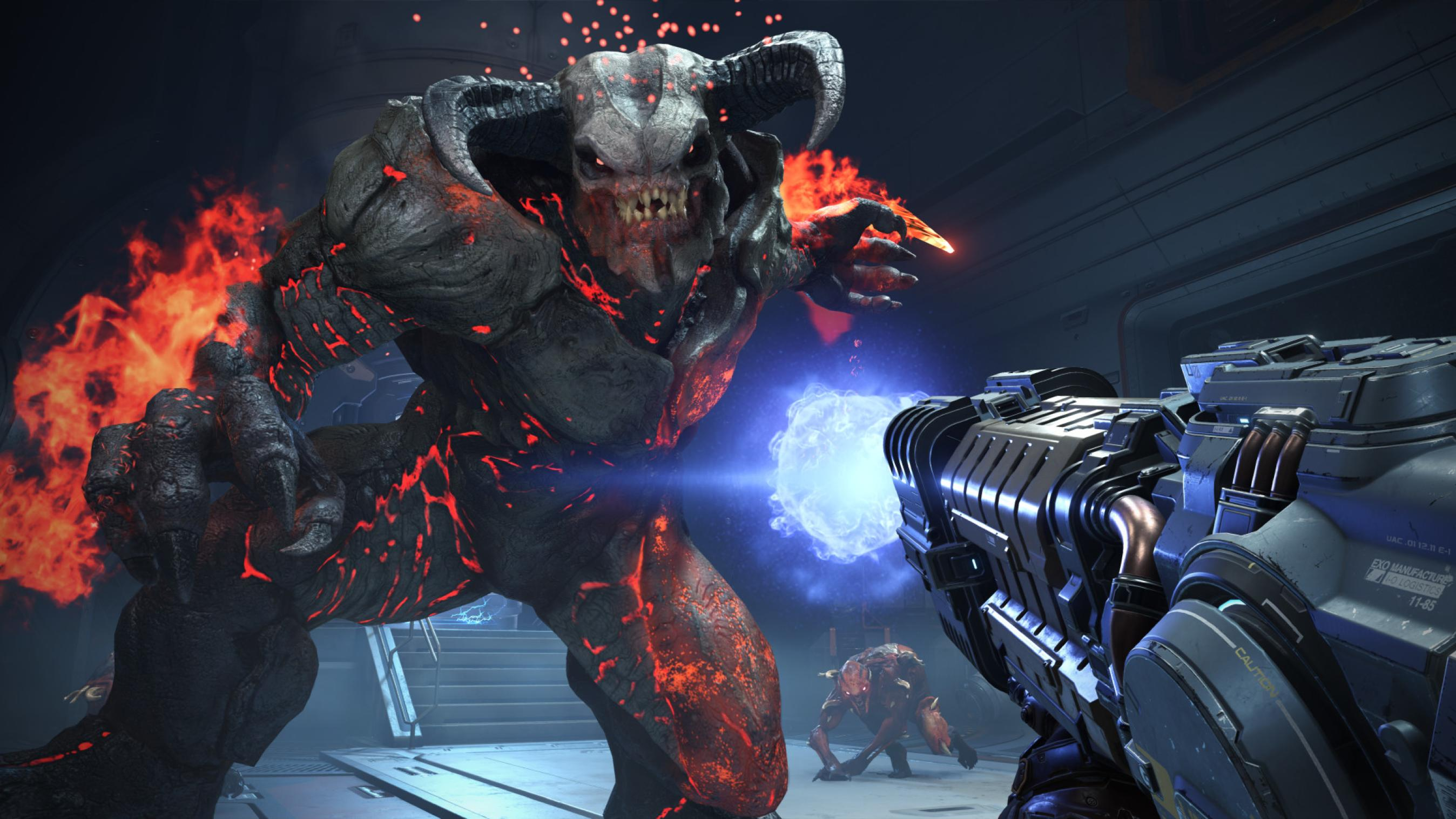 A large demon with horns pulls an arm back to strike. His skin is leathery and black with red embers rising out of various cracks. His hands are on fire. A large gun shoots the demon with blue energy as another, smaller demon watches next to a staircase in the background.