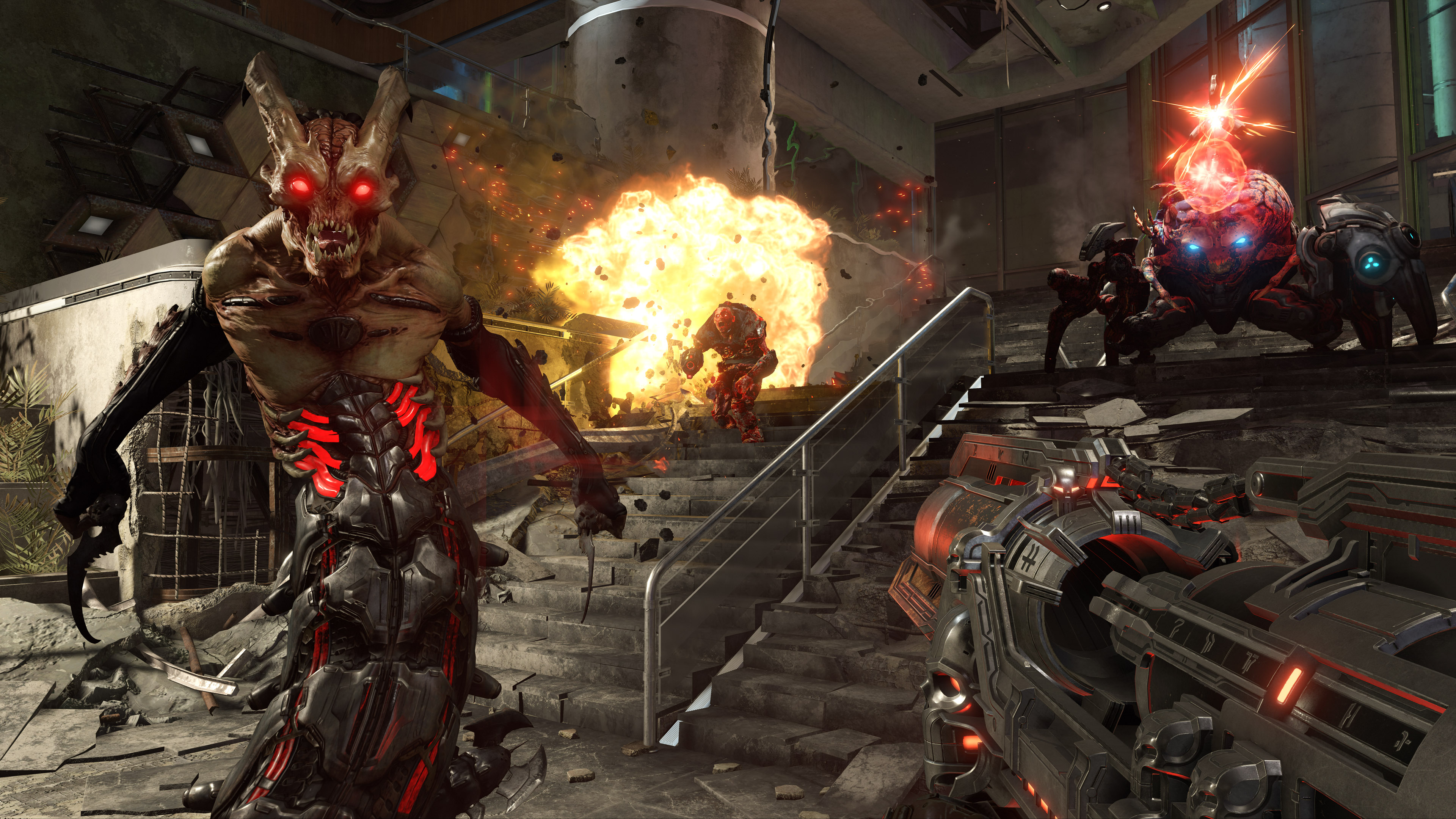 A giant gun is aimed and ready as three demons prepare for battle on a dilapidated staircase with an explosion at the top.