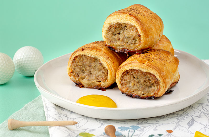 3 sausage rolls on a plate with gold tees and balls in the background