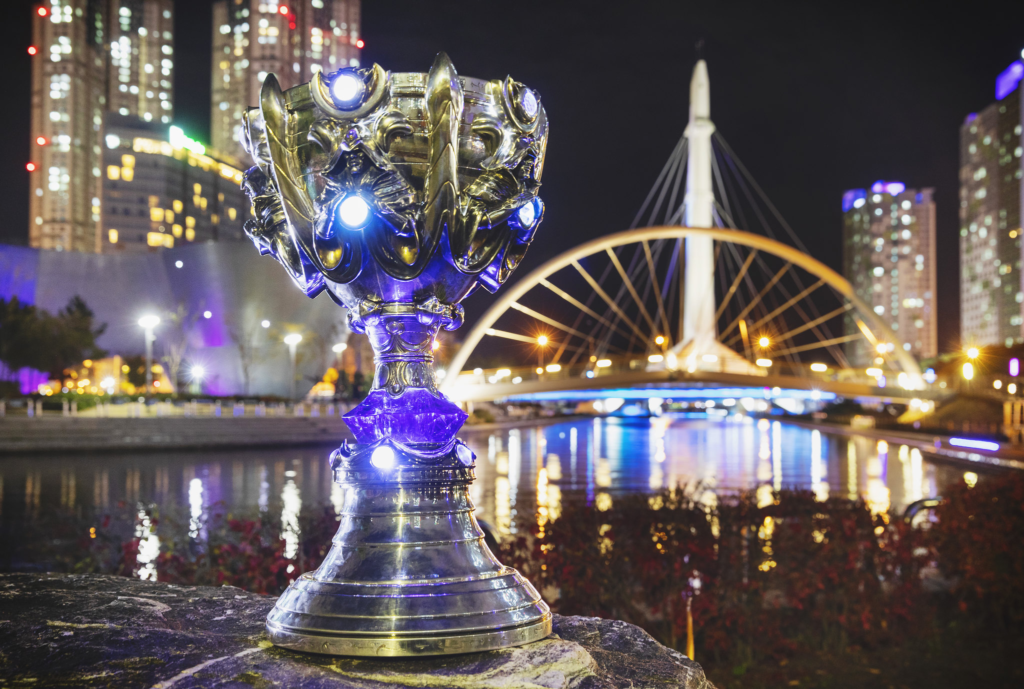 A League of Legends trophy sitting outside in a city at night