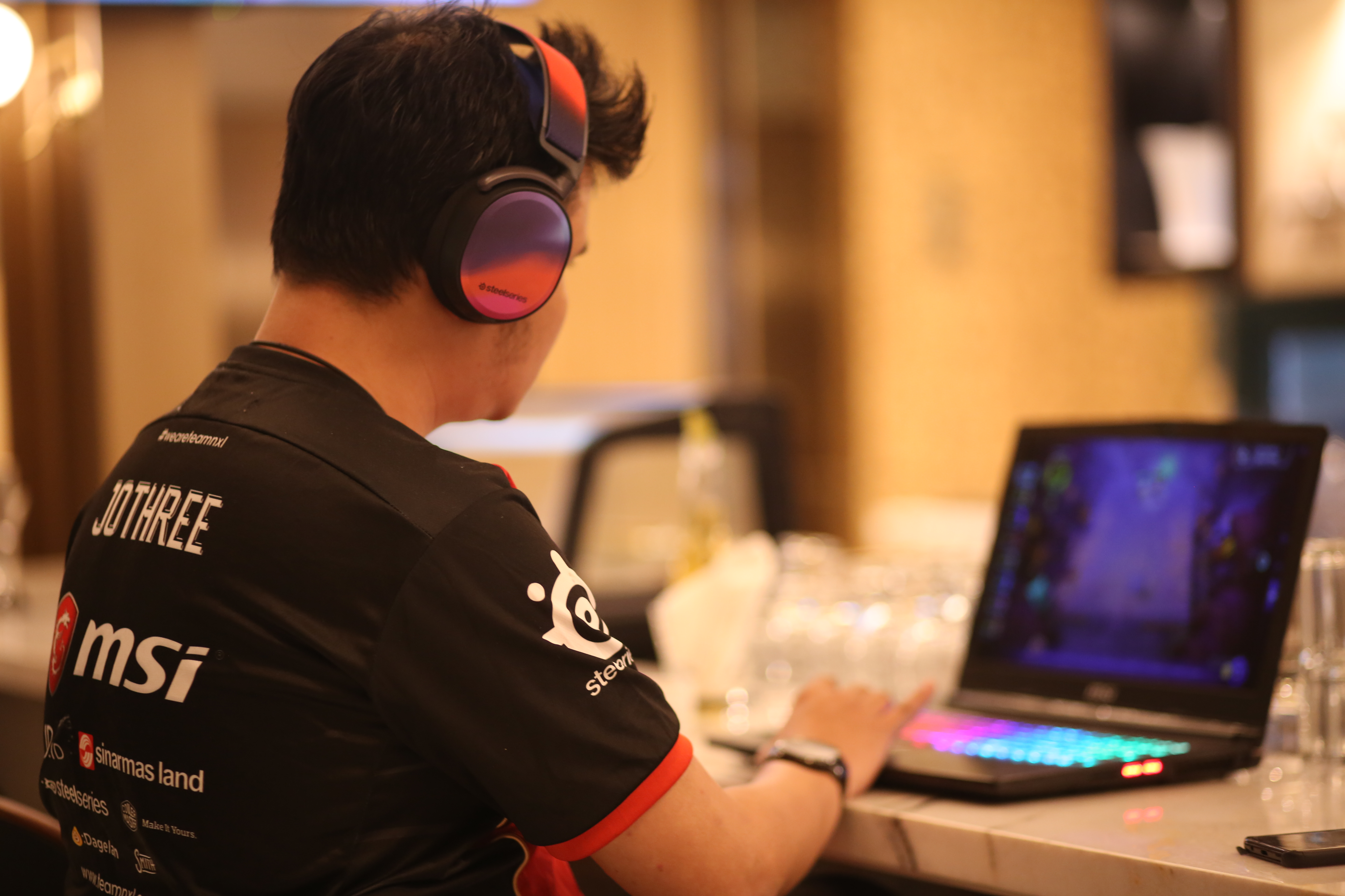 Hearthstone player Joth703 sitting at a laptop playing an unknown game and wearing a SteelSeries headset