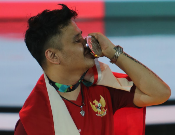 Hearthstone player Joth703 kissing his silver medal on stage at the Asian Games 2018 event