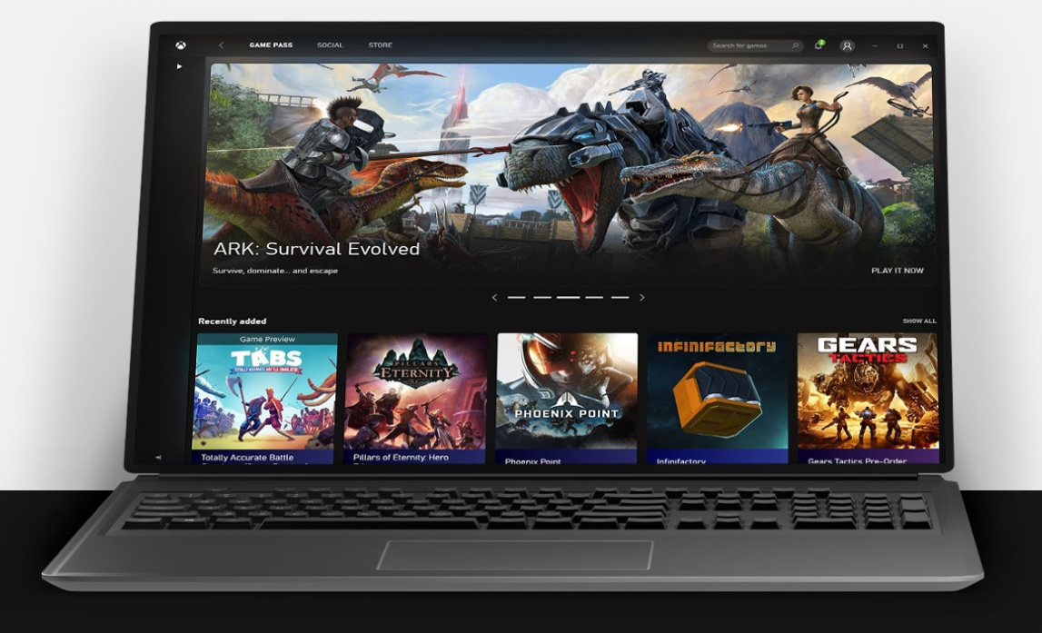 A black laptop computer displays the Xbox Game Pass web portal with several games including ARK Survival Evolved and Gears Tactics