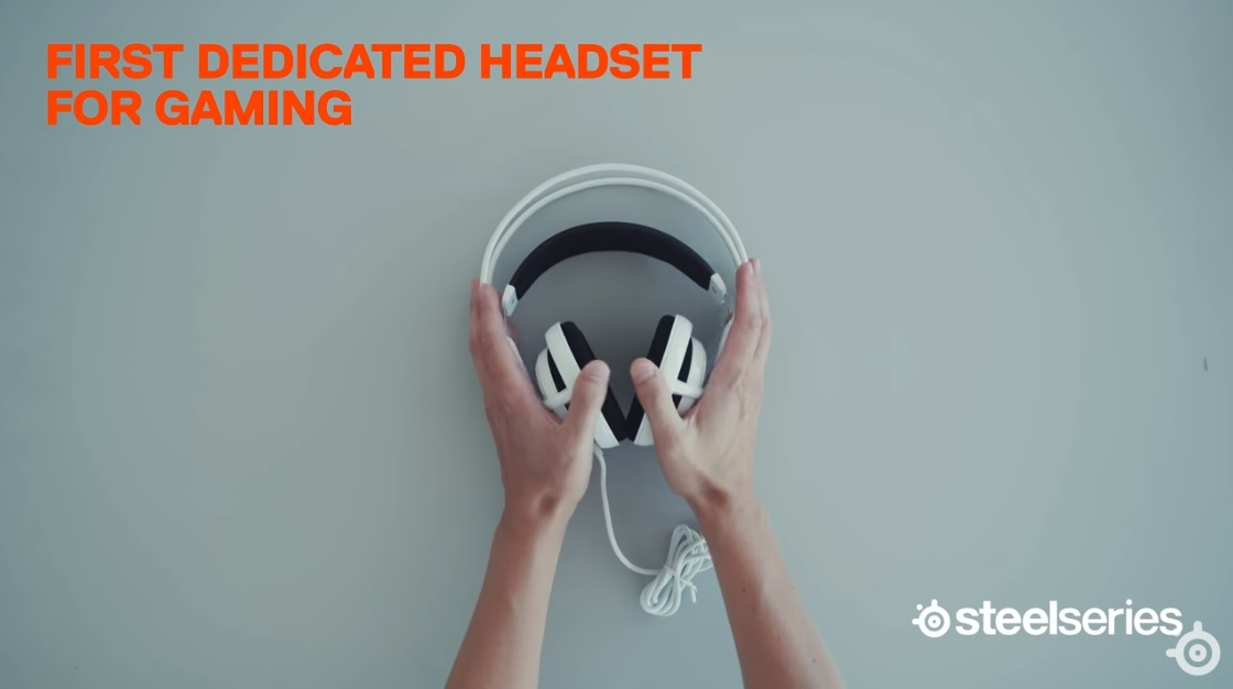 "Hands placing Siberia v1 gaming headphones on a surface with text, ""first dedicated headset for gaming"" and SteelSeries logo in the corner"