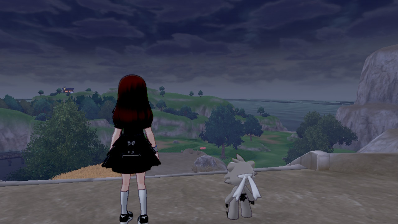 A female Pokemon trainer and Kubfu look out into the distance during particularly stormy weather.