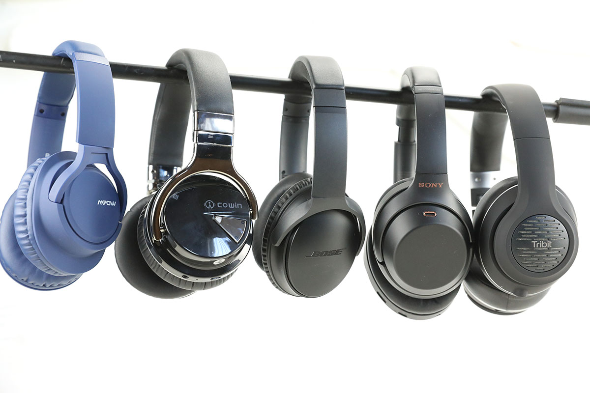 5 pairs of headphones hanging side-by-side on a black pole