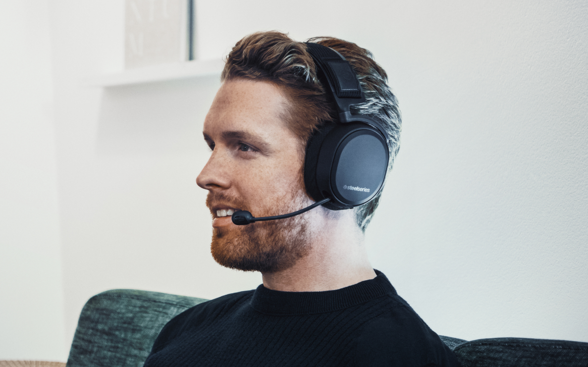 A man sitting on a couch wearing an Arctis Pro Wireless headset