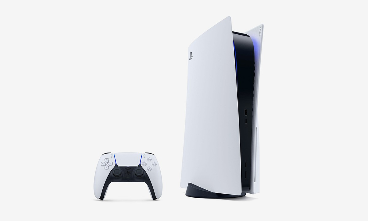 The PlayStation 5 stored horizontally next to a DualSense controller.