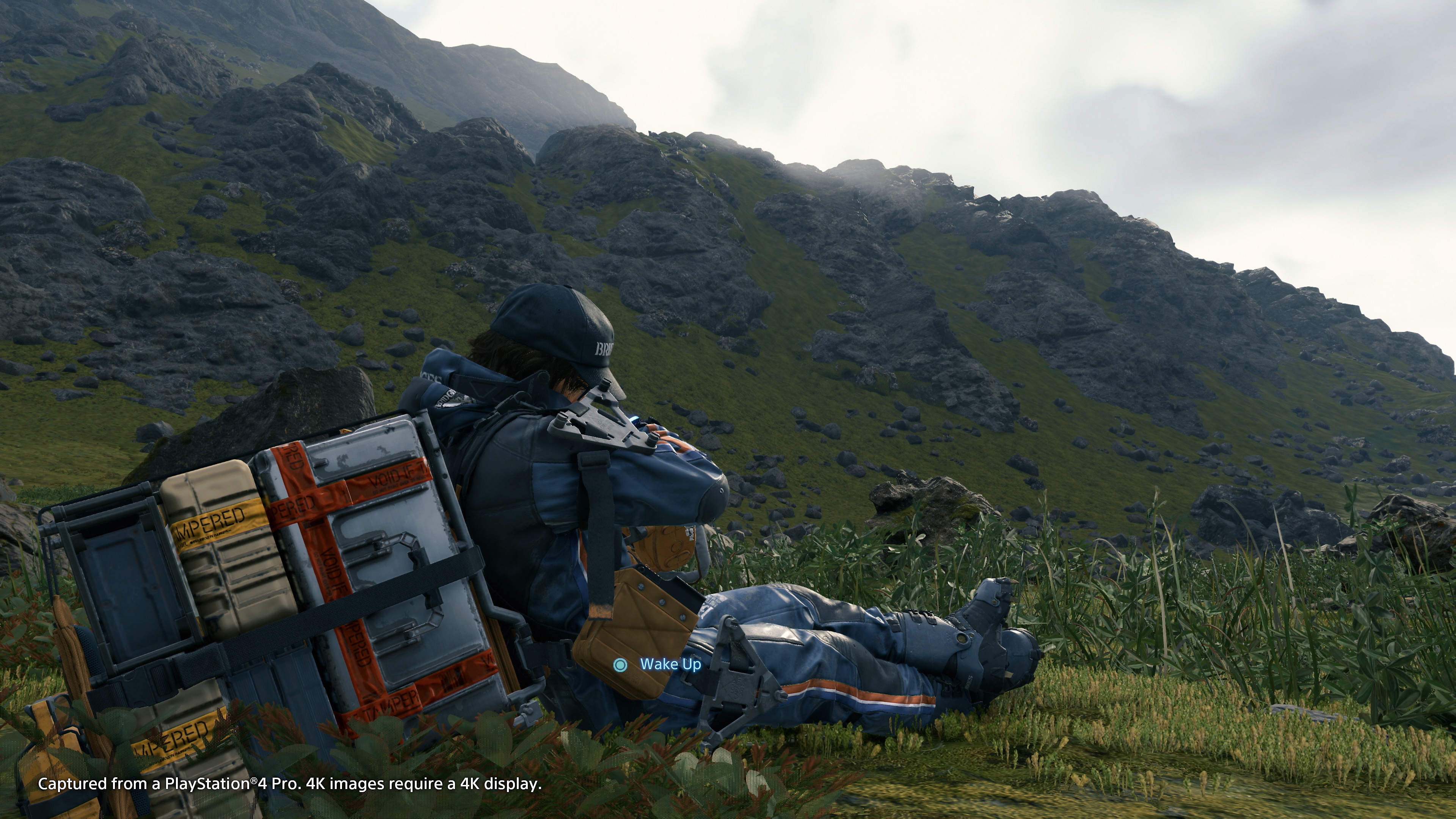 Character from video game Death Stranding sitting in mountains