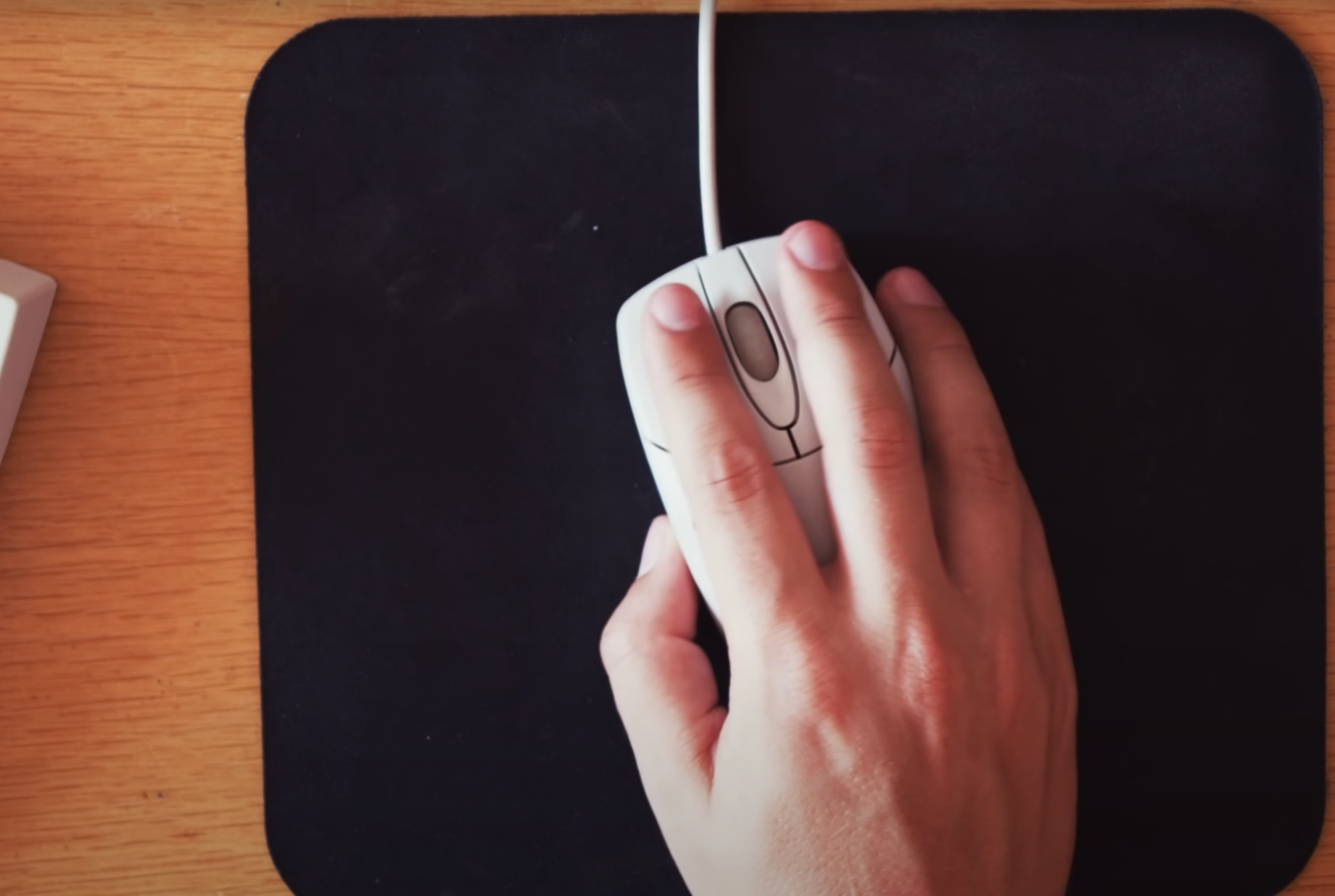 Hand using a trackball mouse on a plain cloth mousepad