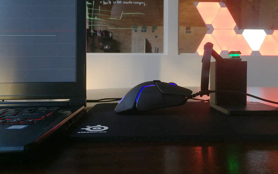 A mouse attached to a machine that lifts the mouse on and off a SteelSeries mousepad