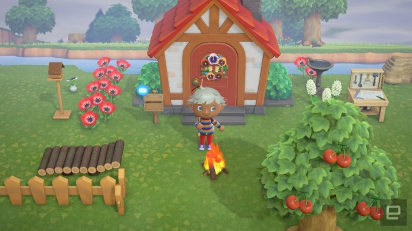 A screenshot from Animal Crossing New Horizons in which a cute character with brown skin and white hair stands outside a small house, smiling and holding a fishing pole over his shoulder. There is a camp fire, apple tree, pile of wood, crafting table, flowers, and other custom decorations.