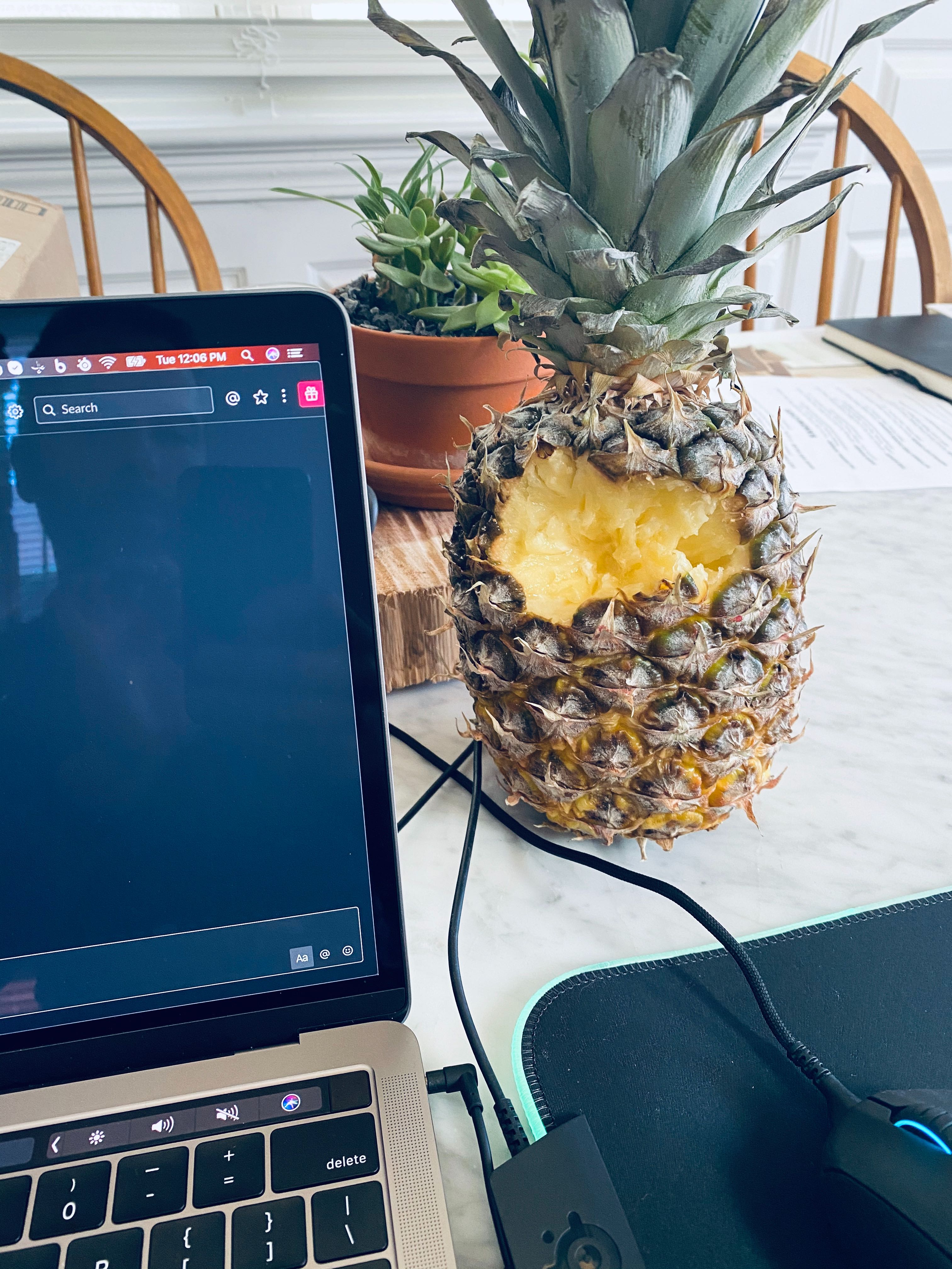 A pineapple with several chunks missing, sitting on a table next to a laptop, mouse, and mousepad