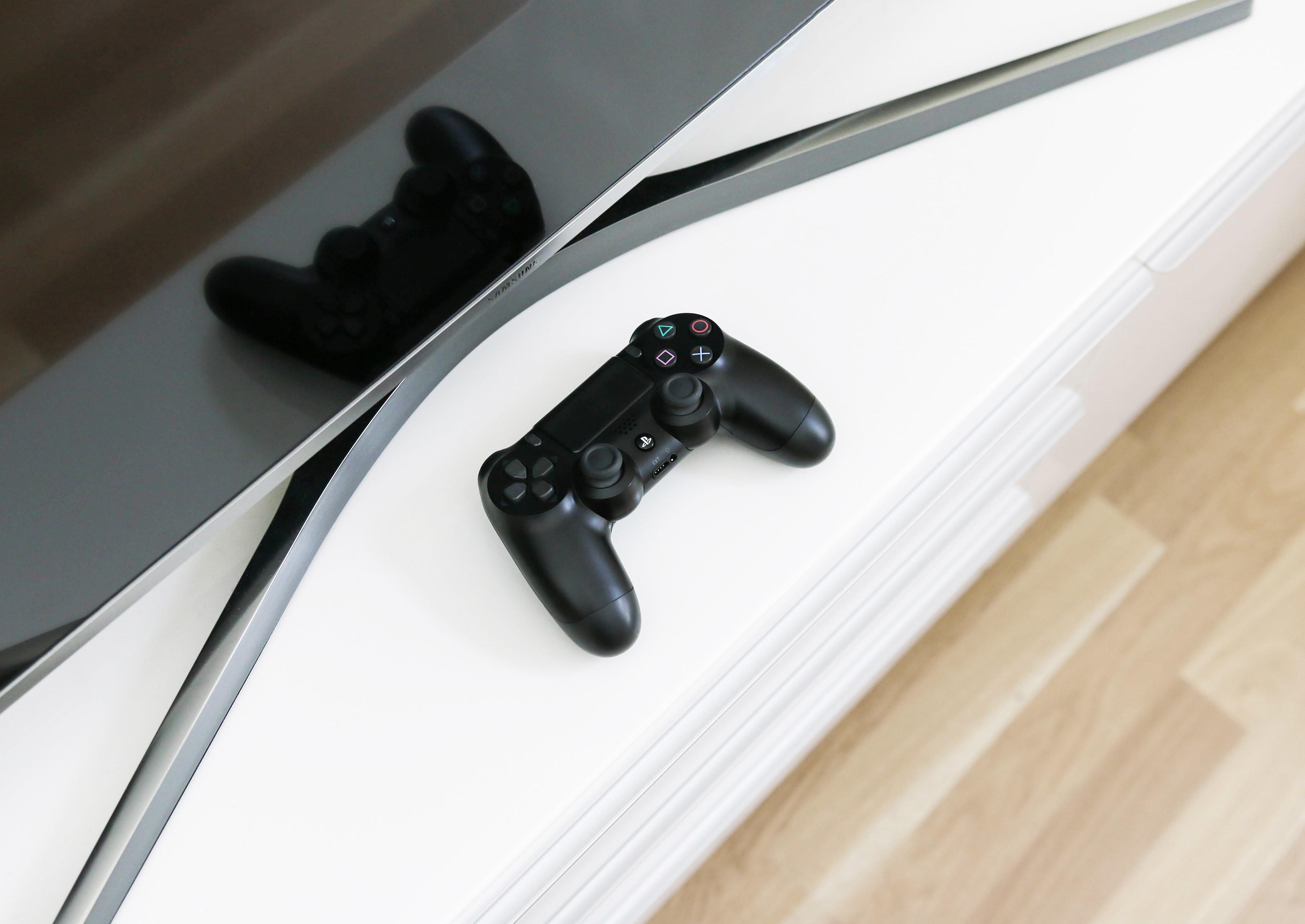 A PlayStation controller near a TV.