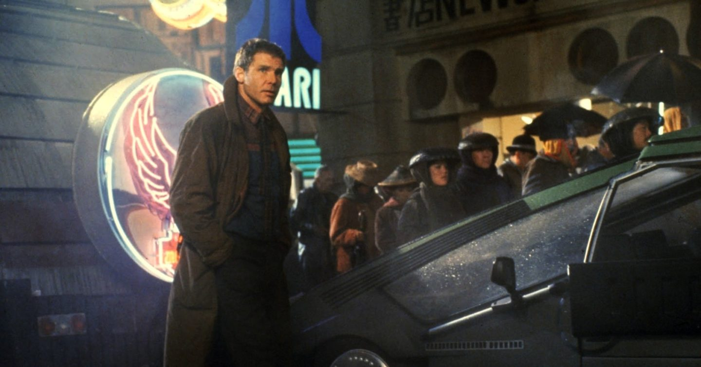A screenshot from Blade Runner. Deckard, a man in a trench coat, stands in front of a futuristic vehicle on a neon-filled street. A crowd of passersby carry umbrellas. A neon sign behind him says Atari.