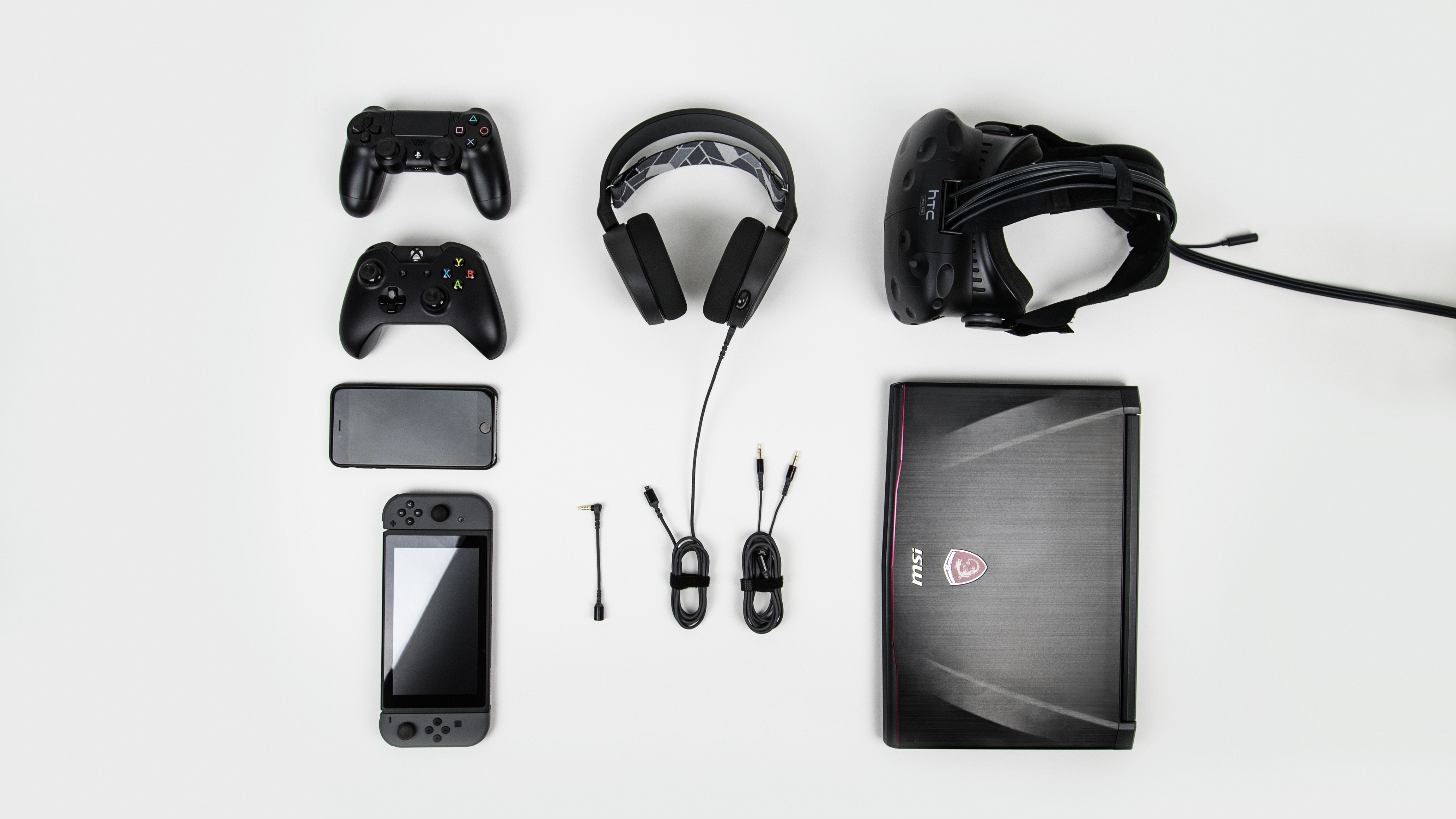 Neatly layed out PlayStation controller, XBOX controller, iPhone, Nintendo Switch, HTC Vive, MSI laptop, and SteelSeries headset with connectors