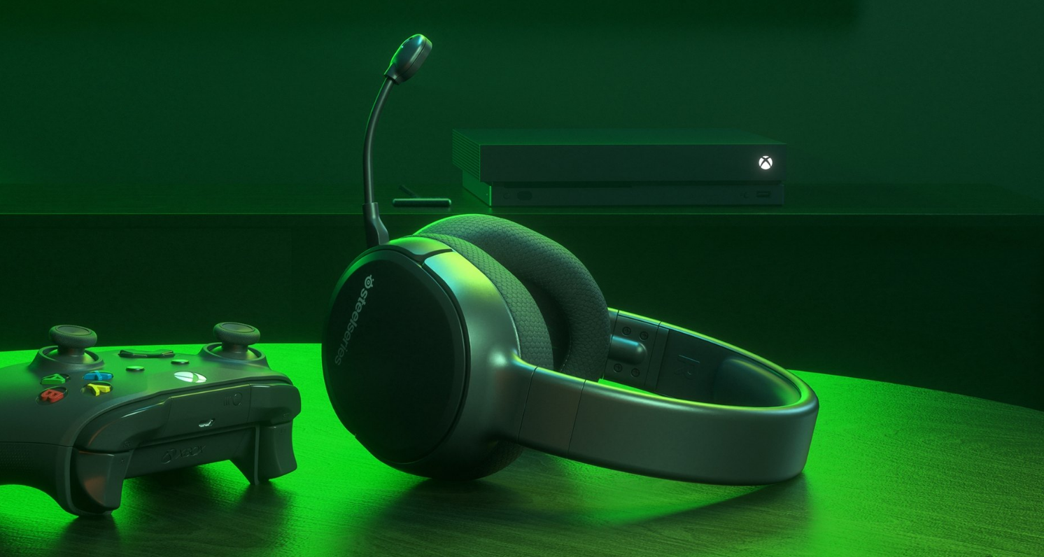 Arctis 1 Wireless for Xbox headset laying on a table with a controller in front of a TV