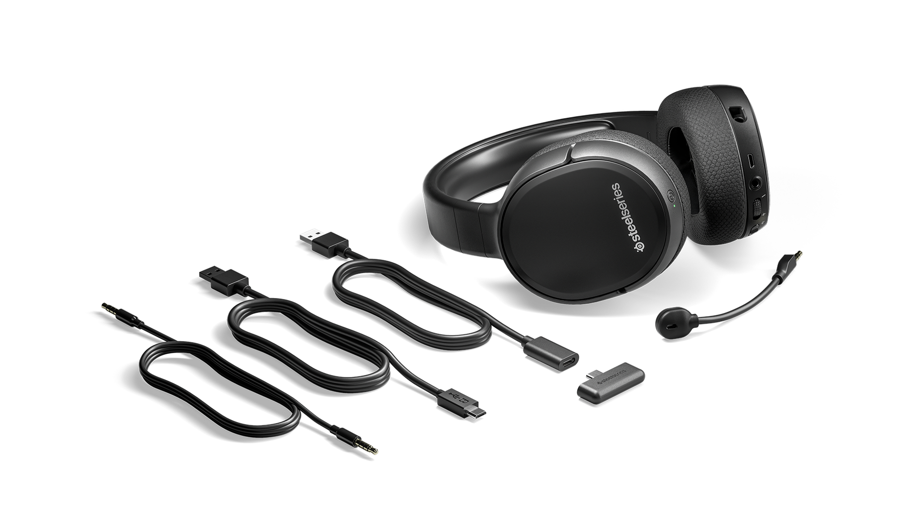 The Arctis 1 Wireless gaming headset surrounded by all the box contents including extra cables and the wireless dongle.