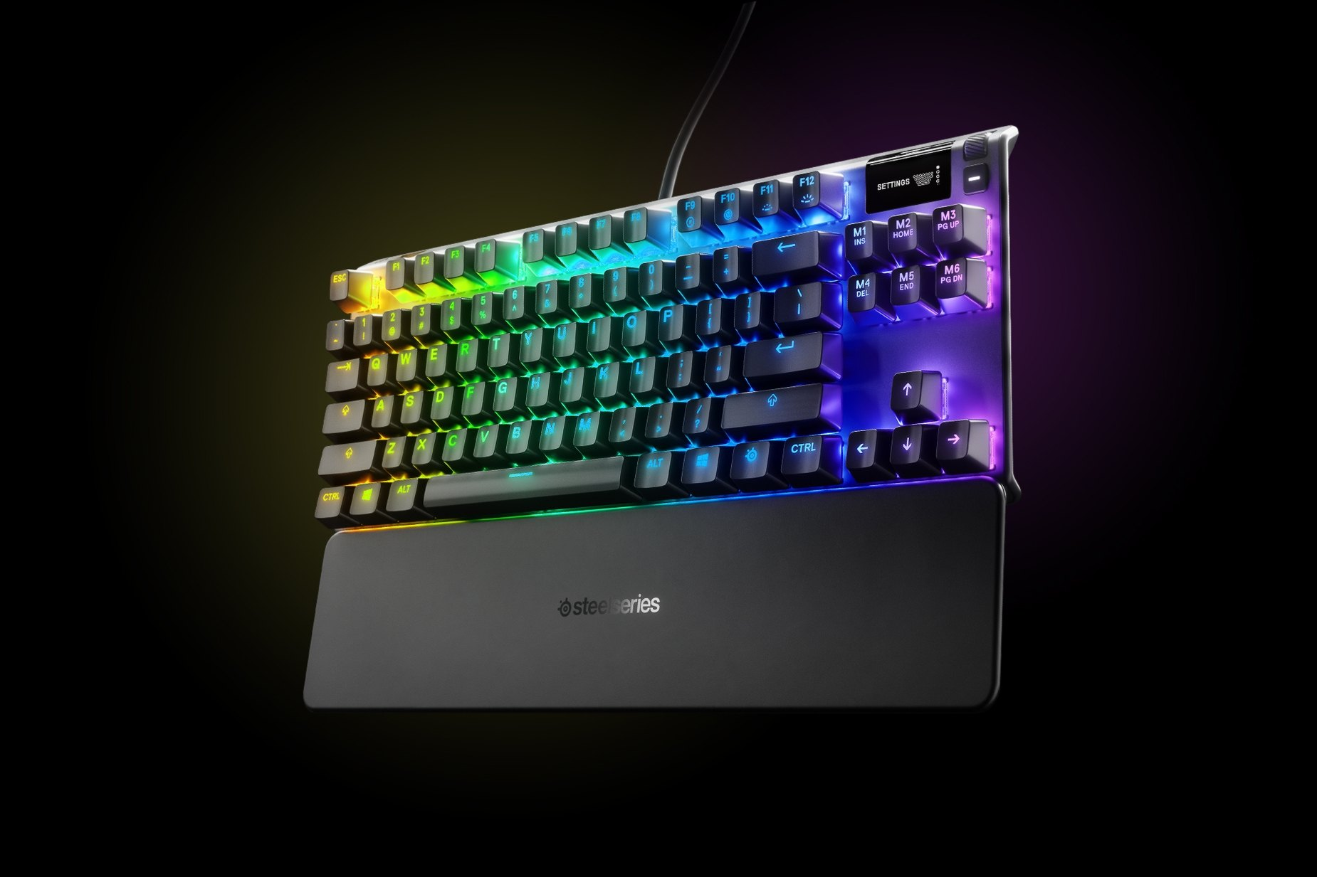 英国英语-Apex 7 TKL (Blue Switch) gaming keyboard with the illumination lit up on dark background, also shows the OLED screen and controls used to change settings and adjust audio