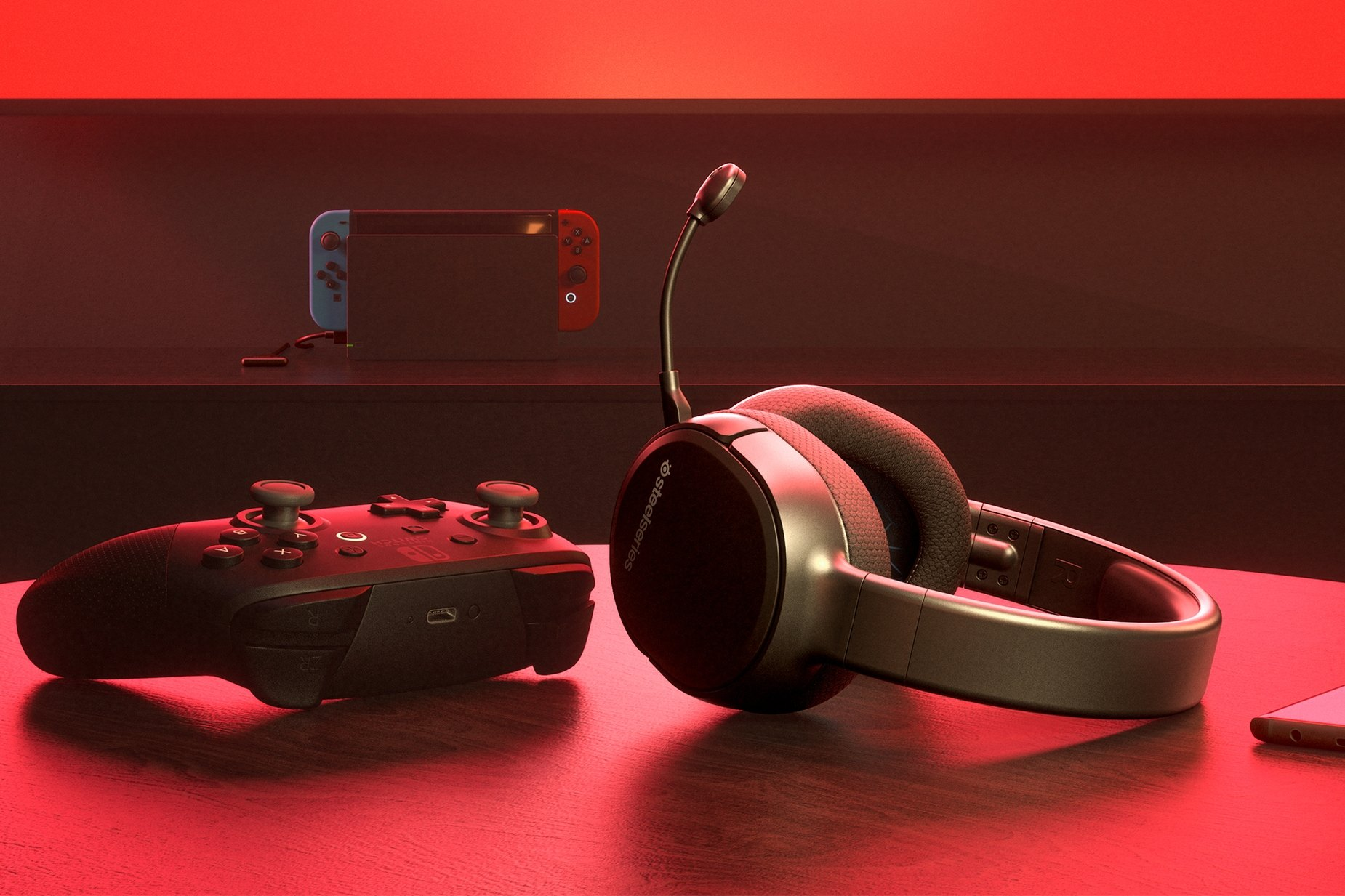Arctis 1 Wireless for Switch gaming headset on table with a Nintendo Switch Pro controller and a Switch game console in the background