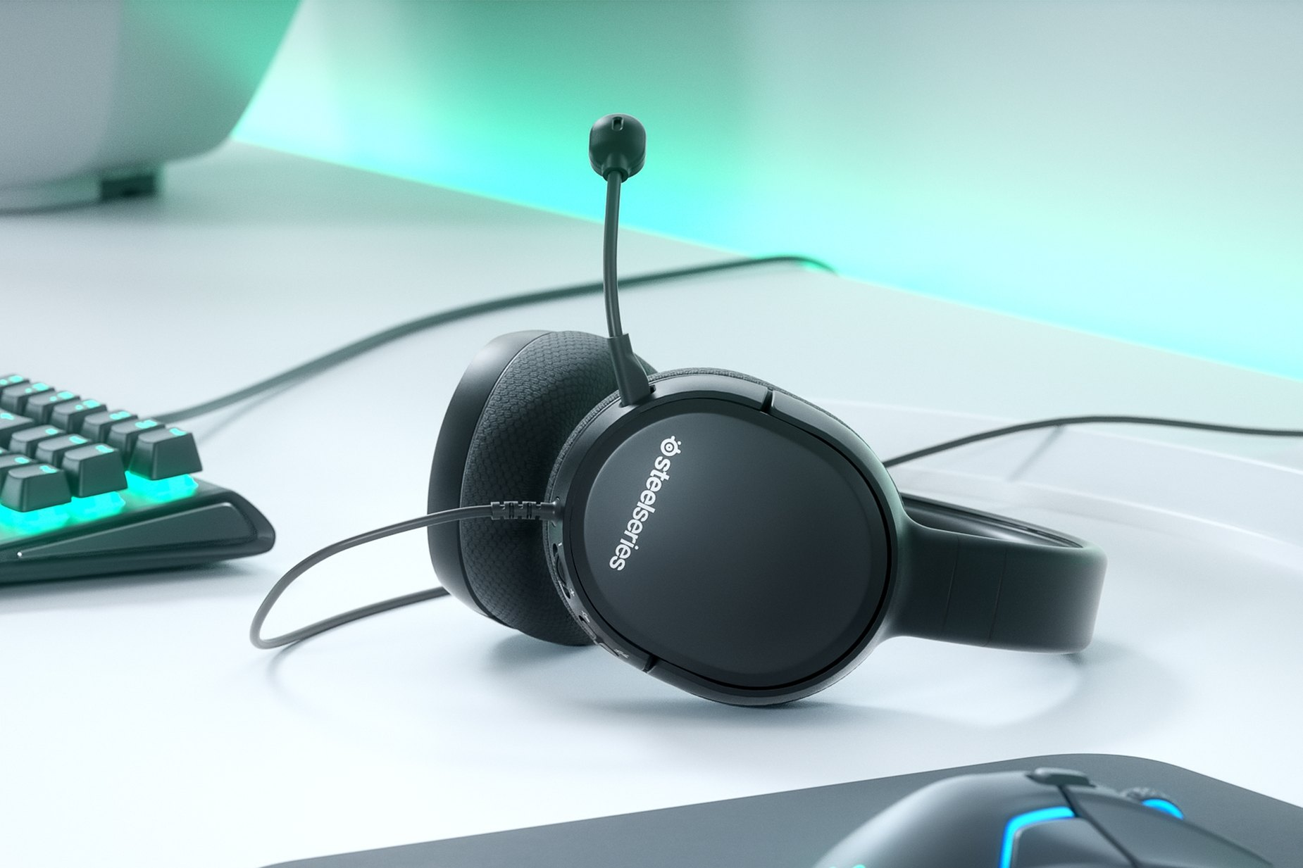 Arctis 1 gaming headset on a desk with a full SteelSeries setup including a mouse, mousepad, and keyboard